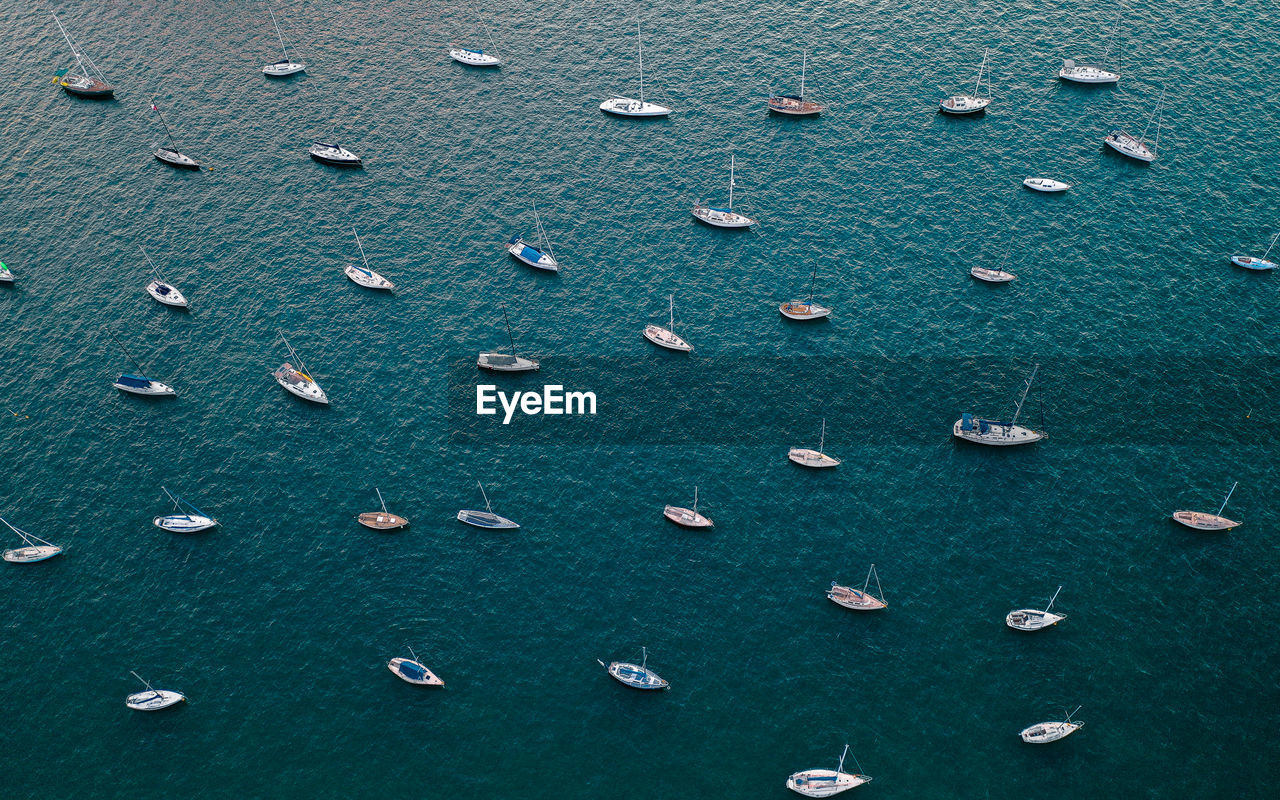 High angle view of sailboats moored in sea or in a bay