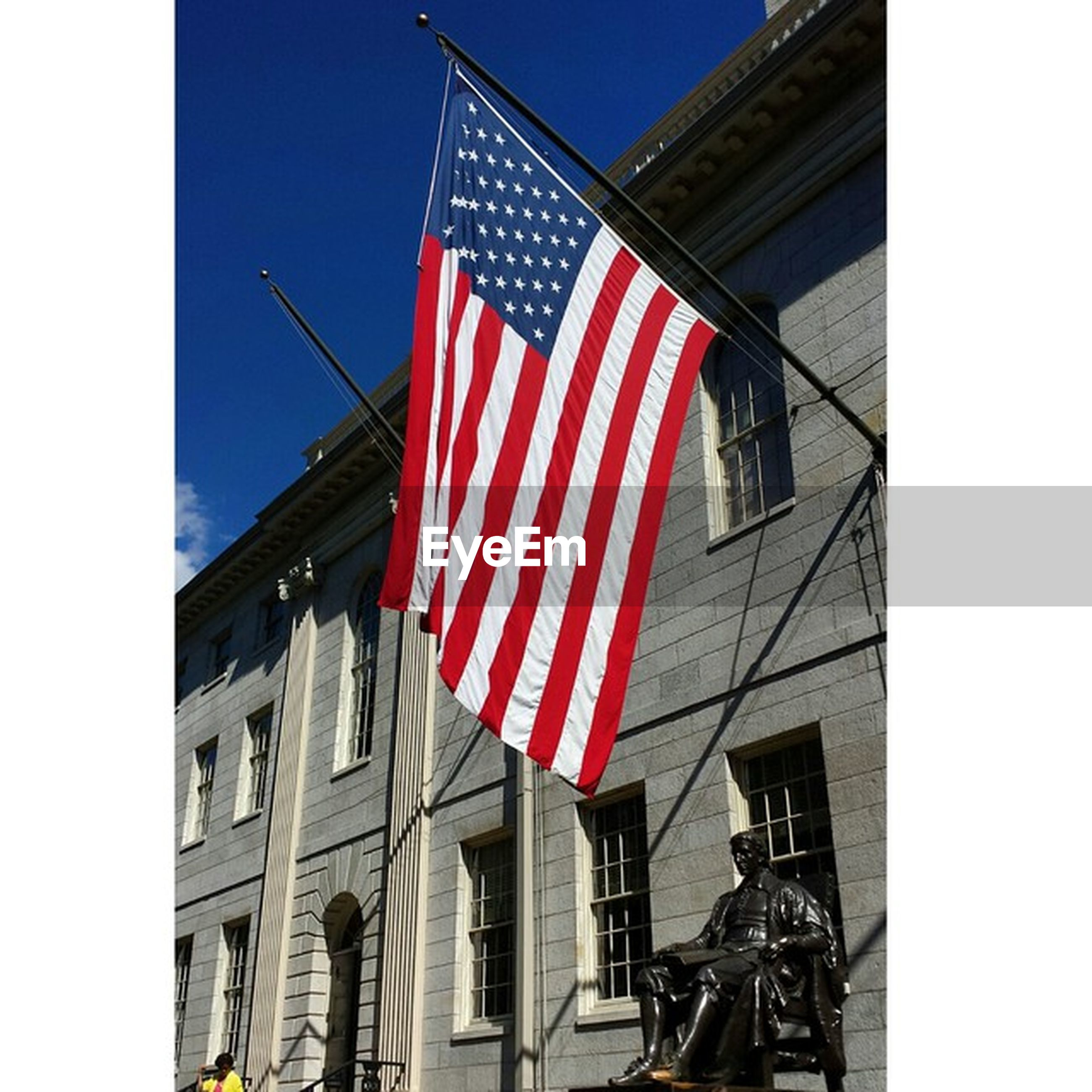 flag, patriotism, national flag, identity, american flag, building exterior, architecture, built structure, low angle view, culture, red, clear sky, city, wind, striped, pride, sky, pole, day, outdoors