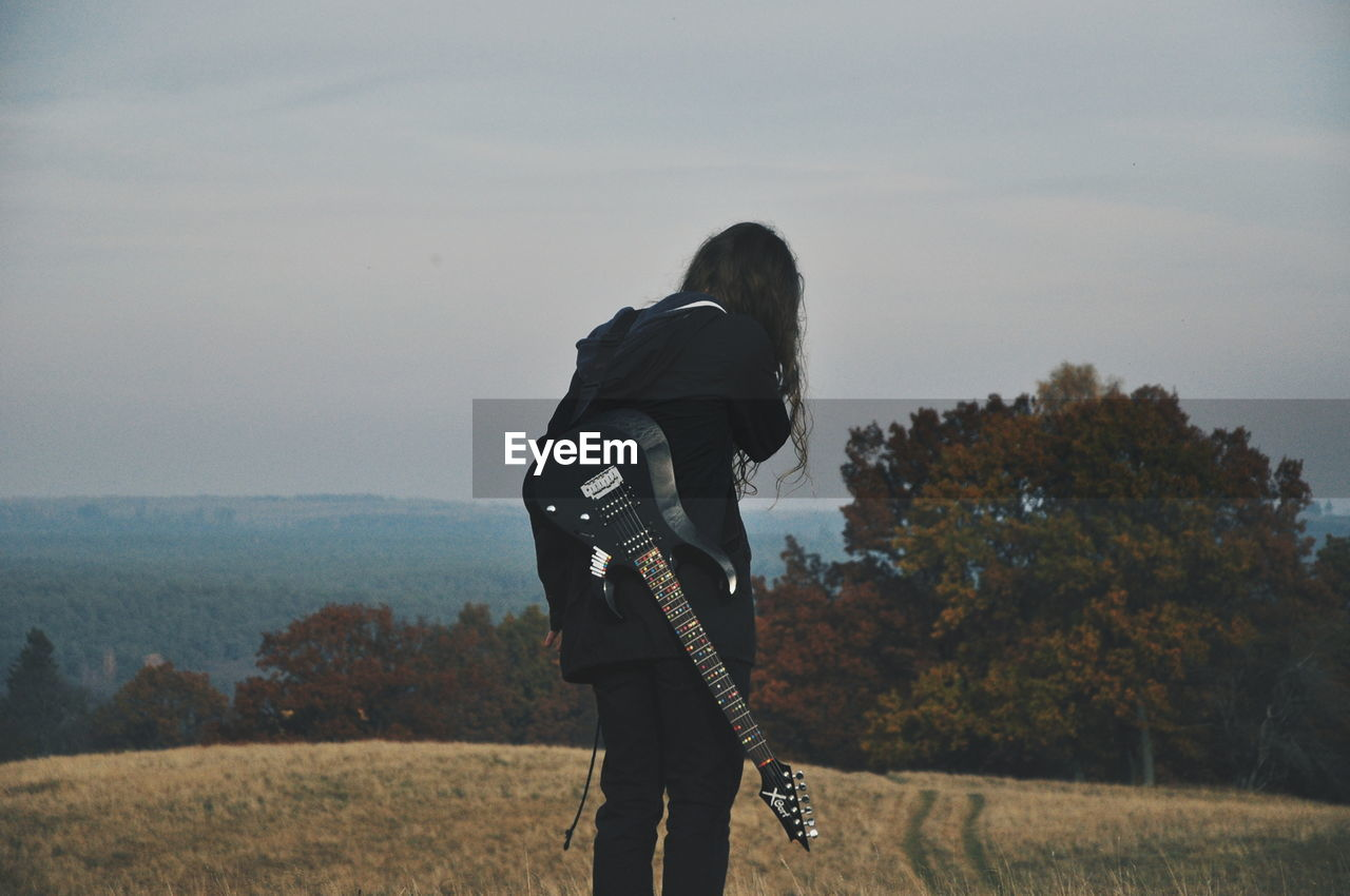 Rear view of man standing on field with guitar