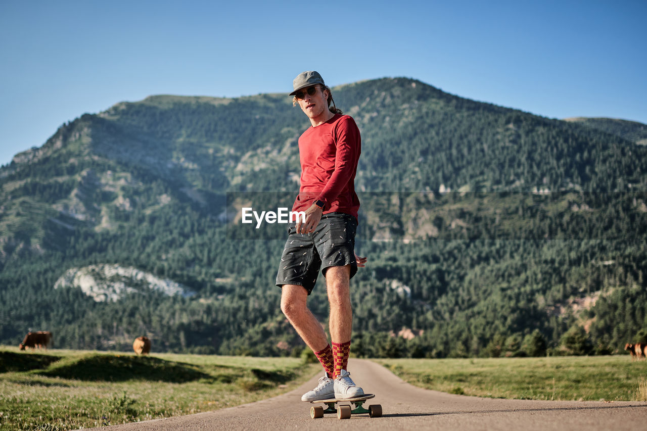 FULL LENGTH OF YOUNG MAN AGAINST MOUNTAIN RANGE