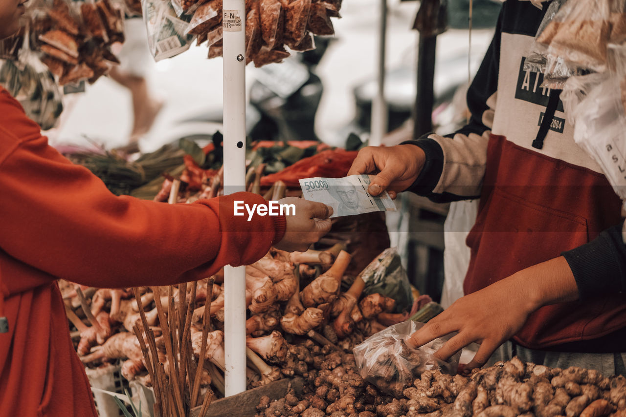 Hands holding vegetables for sale at market stall