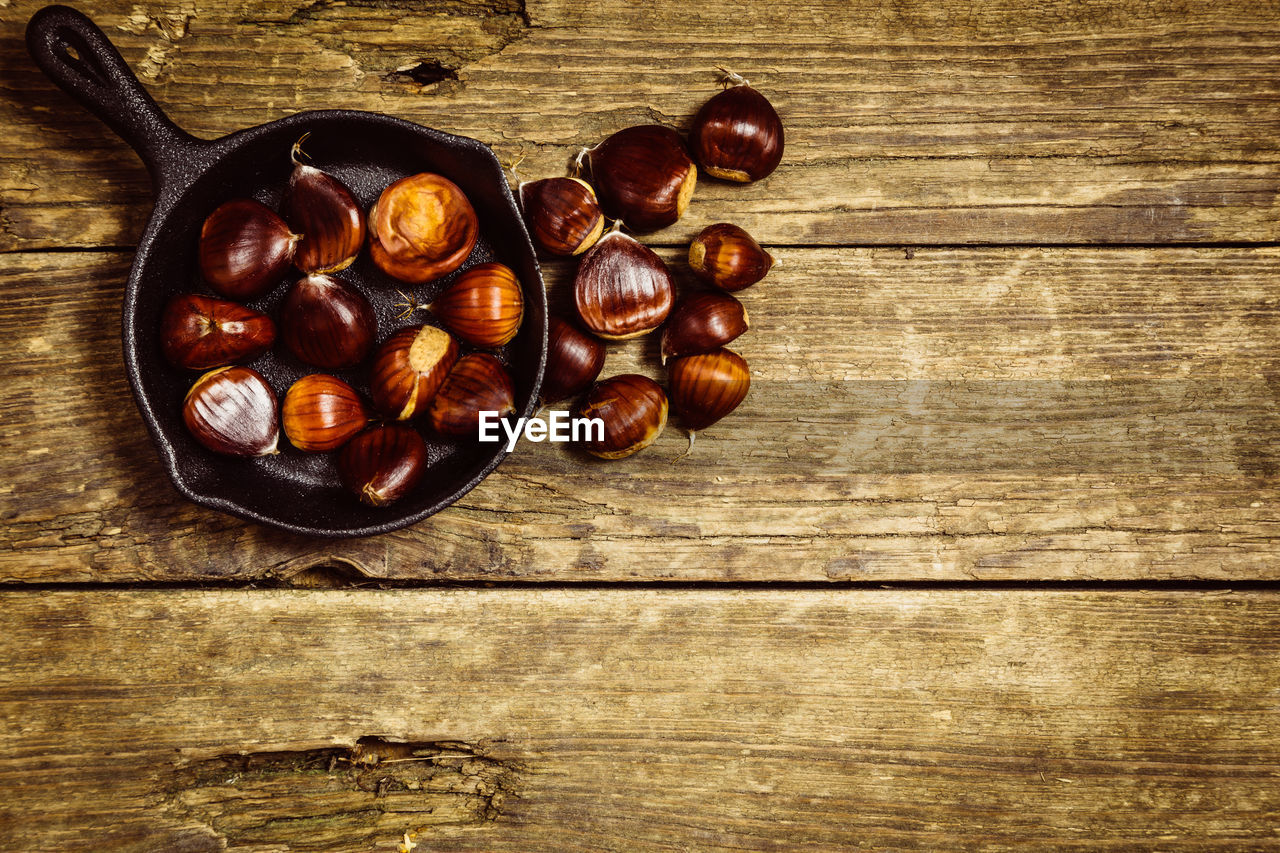 food and drink, food, wood - material, directly above, freshness, table, brown, healthy eating, still life, indoors, chestnut, nut - food, large group of objects, wellbeing, nut, no people, high angle view, chestnut - food, fruit, close-up