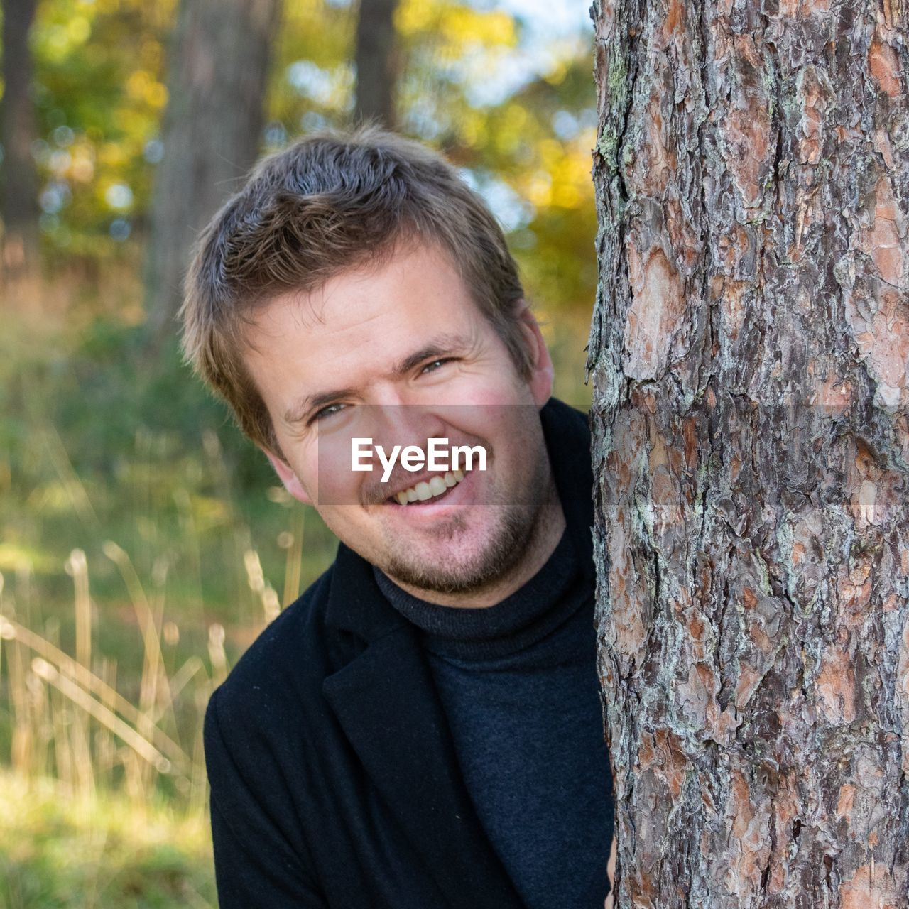 Portrait of smiling young man by tree trunk