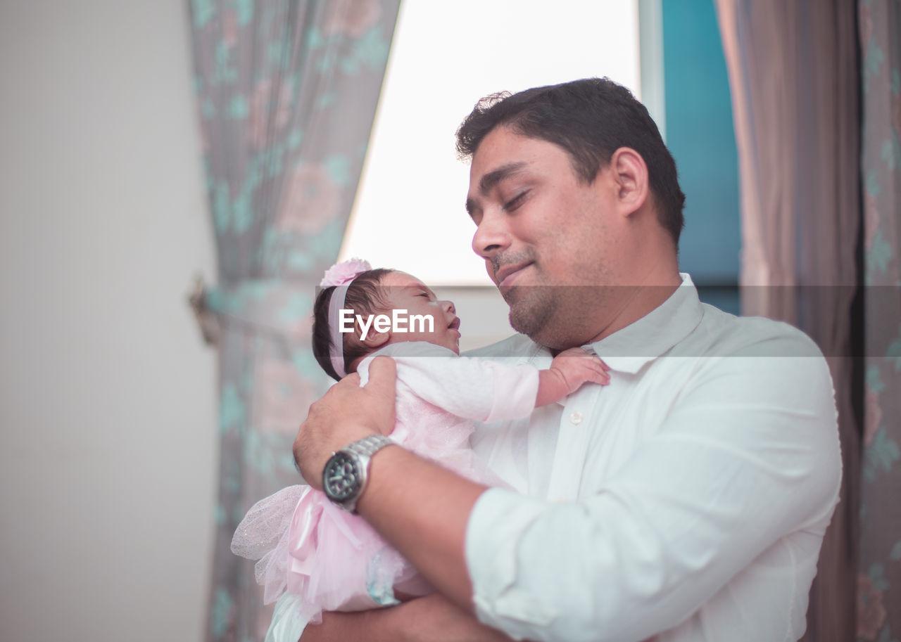 Smiling Man Carrying Newborn Daughter At Home