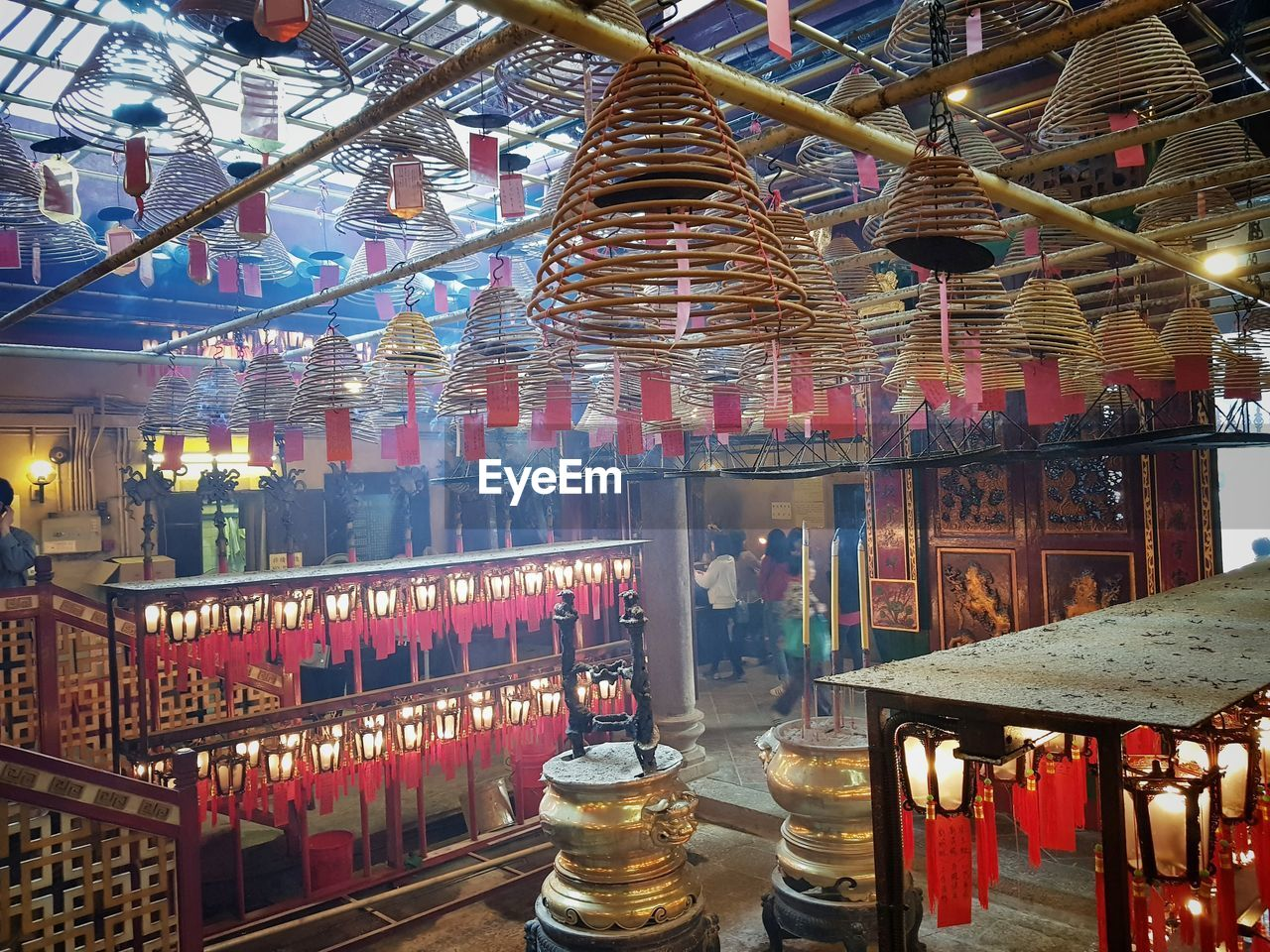large group of objects, indoors, lighting equipment, arrangement, illuminated, no people, abundance, religion, spirituality, in a row, place of worship, belief, container, architecture, built structure, incense, retail, choice, variation, bar counter, altar, electric lamp