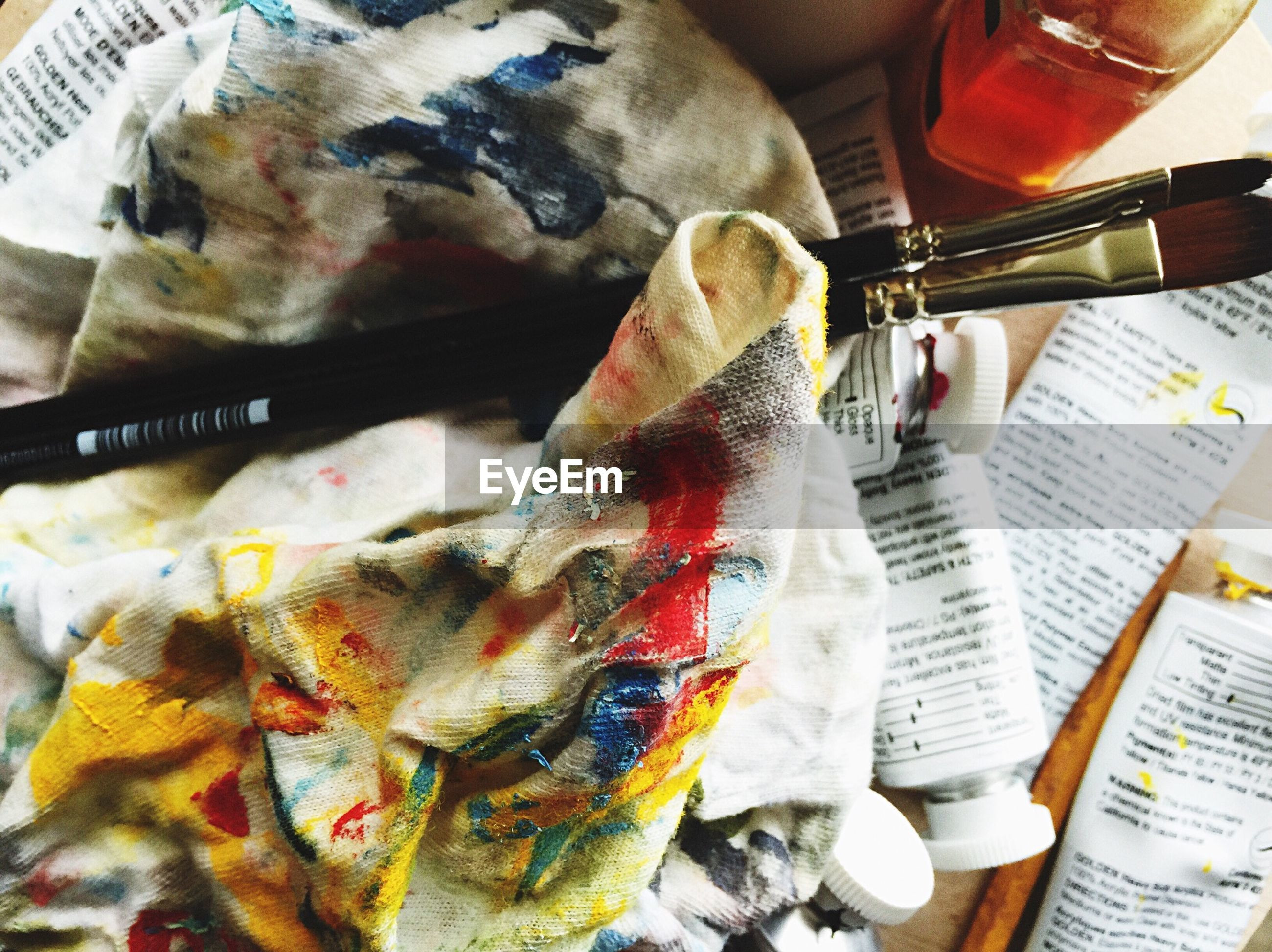 High angle view of messy fabric and paint brush on table
