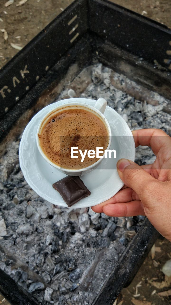 coffee cup, coffee - drink, drink, human hand, food and drink, refreshment, human body part, saucer, cup, holding, high angle view, freshness, one person, frothy drink, close-up, table, men, indoors, cafe, real people, cappuccino, day, food, froth art, people