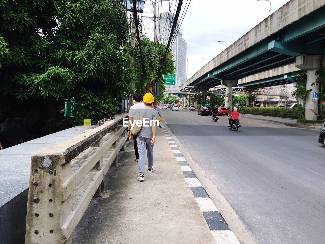 Rear view of men walking on footpath by street in city