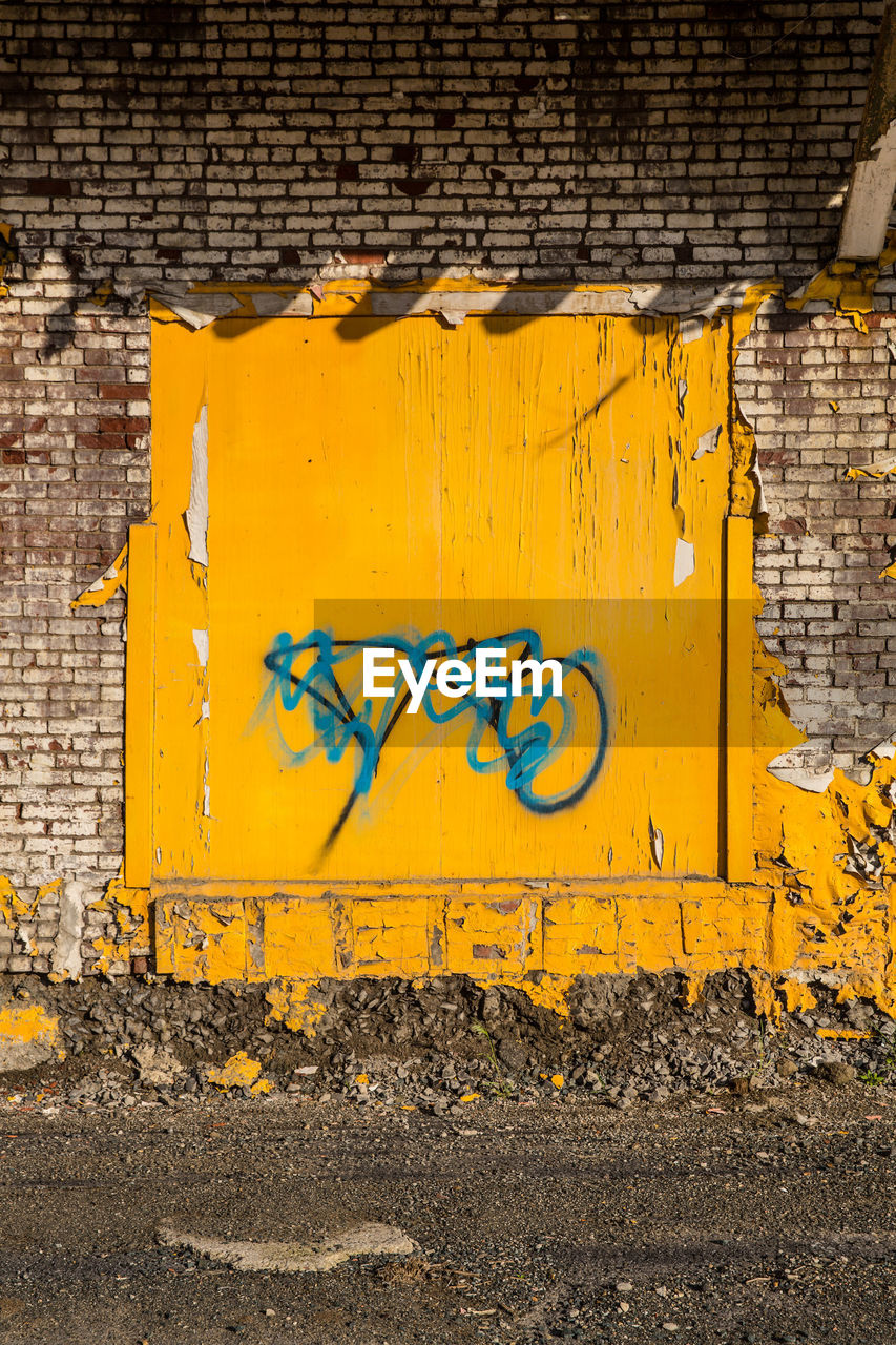 yellow, architecture, wall - building feature, no people, built structure, graffiti, building exterior, wall, day, brick wall, damaged, paint, brick, sign, old, outdoors, city, creativity, communication, art and craft