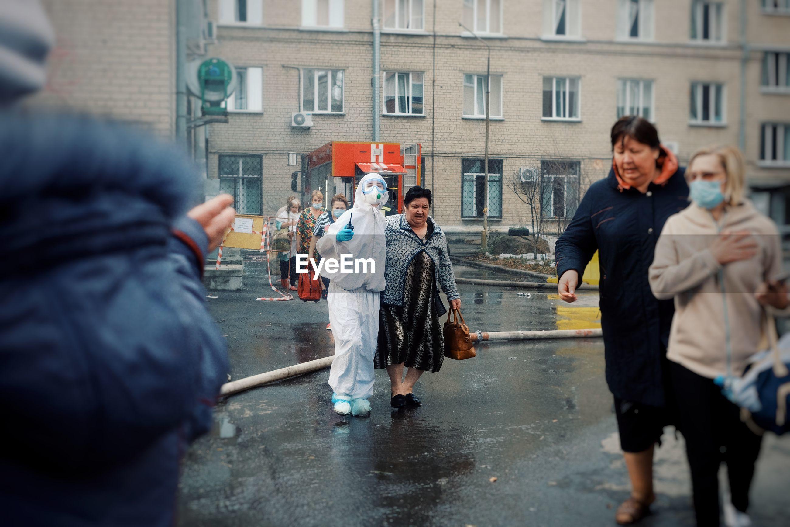 PEOPLE ON WET STREET IN RAIN