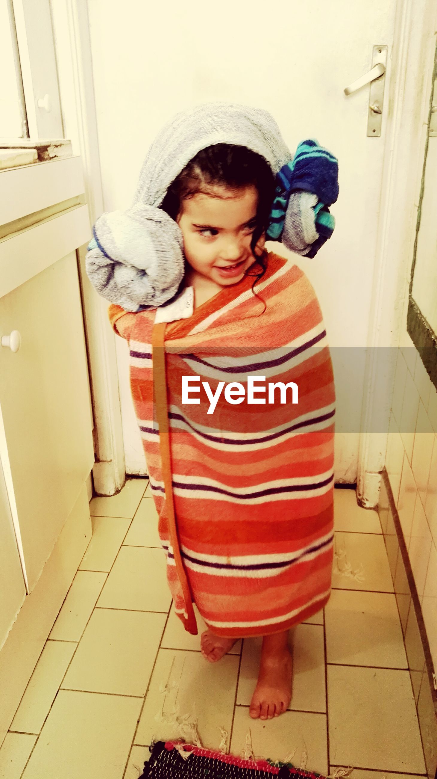 Full length of girl wrapped in towel standing on floor against door at home