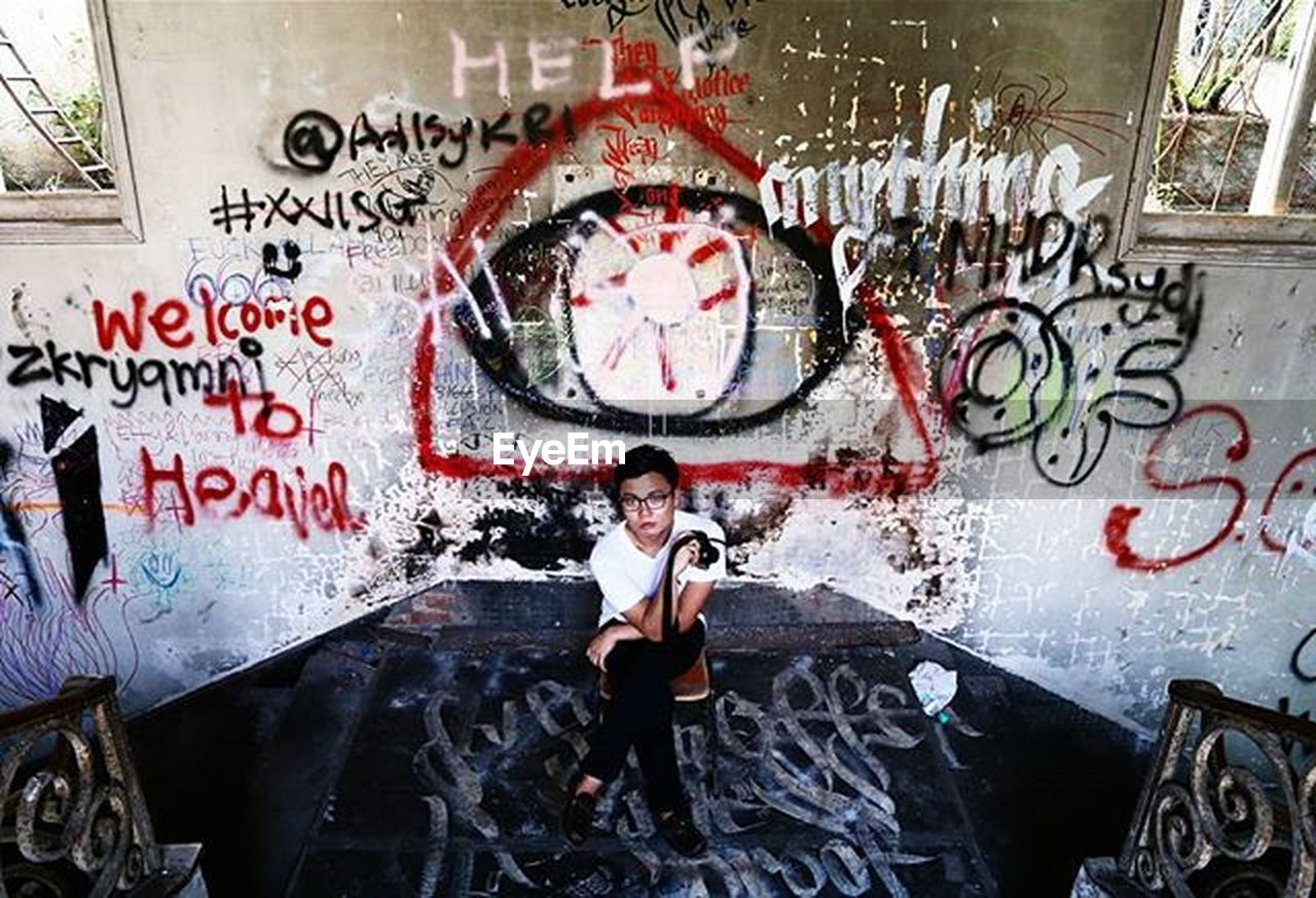 graffiti, looking at camera, front view, one person, standing, portrait, communication, full length, day, wireless technology, adults only, adult, one woman only, outdoors, people
