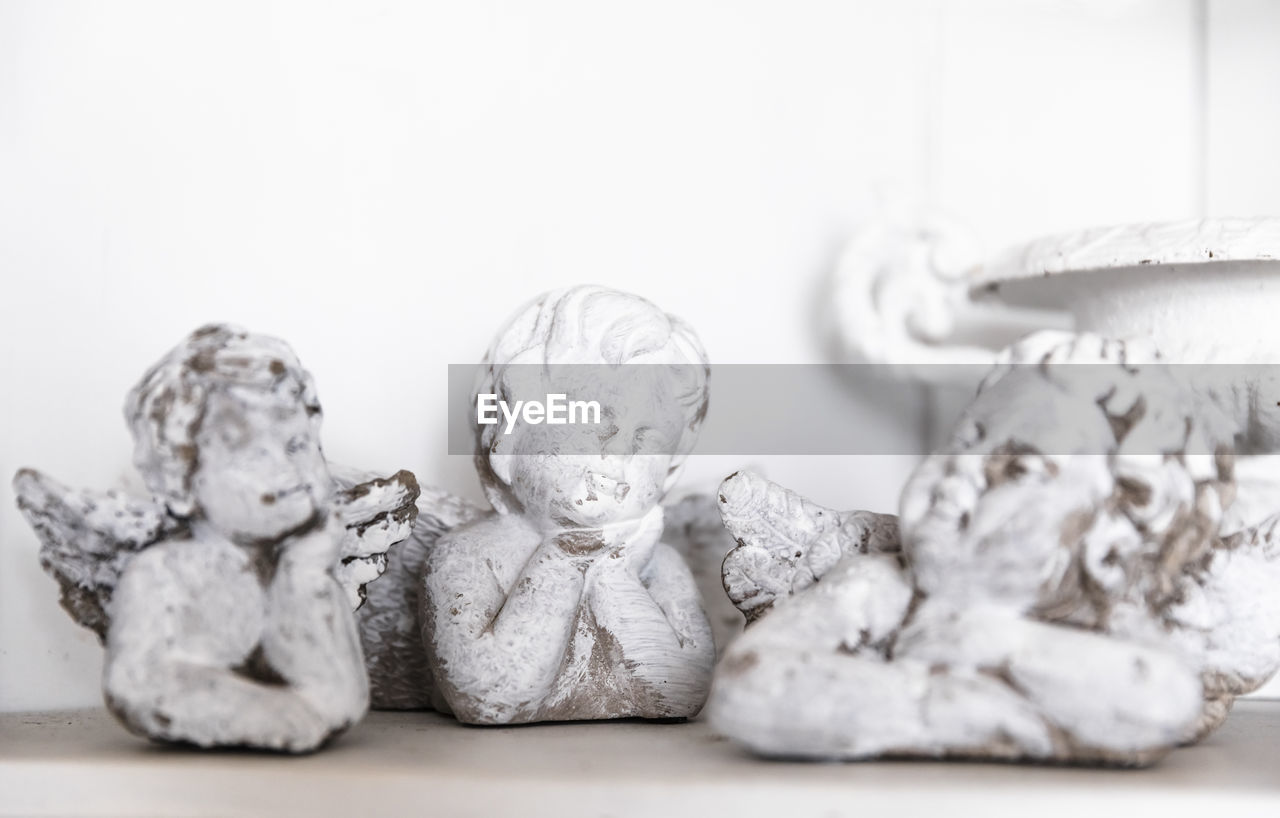 Close-Up Of Angel Figurines On Table Against Wall