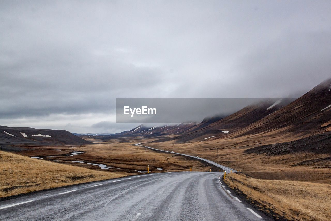 Country Road Leading Towards Mountains Against Cloudy Sky