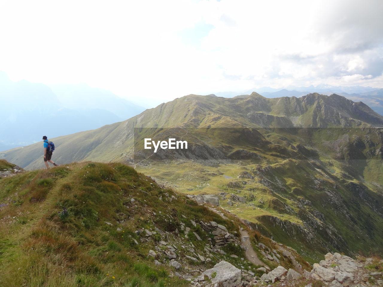 Hiker walking on peak by mountains against sky