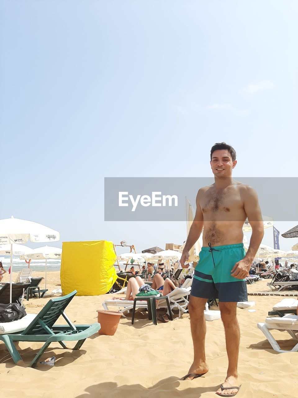 sky, beach, shirtless, young adult, land, young men, men, one person, looking at camera, copy space, full length, lifestyles, real people, nature, incidental people, chair, leisure activity, day, front view, shorts