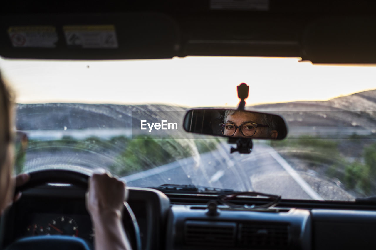Reflection Of Senior Woman Seen In Rear-View Mirror