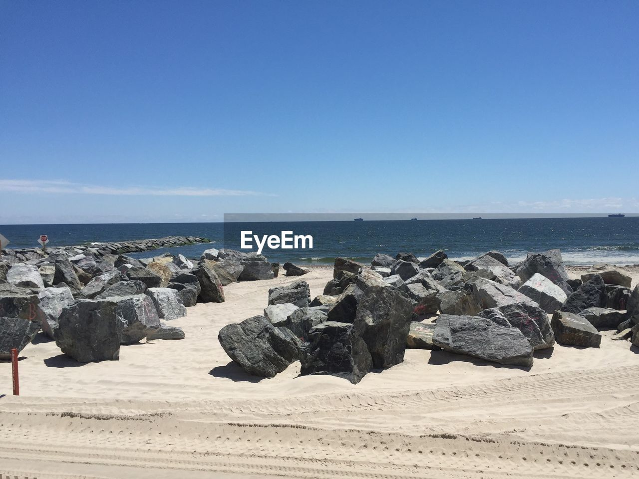 sea, beach, horizon over water, sand, nature, blue, clear sky, water, scenics, day, rock - object, beauty in nature, sky, tranquil scene, sunlight, tranquility, outdoors, no people