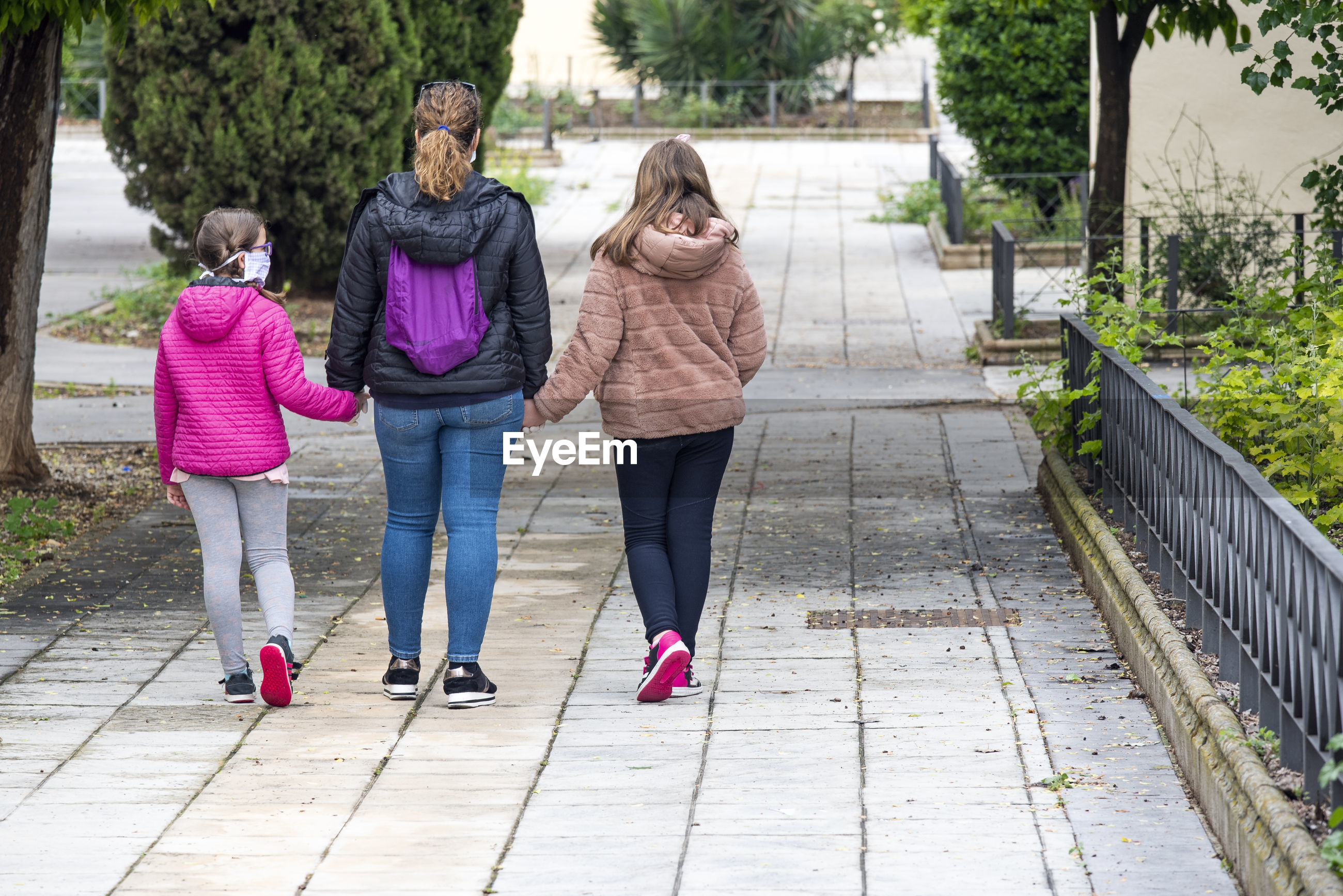 Rear view of mother with daughters walking on footpath