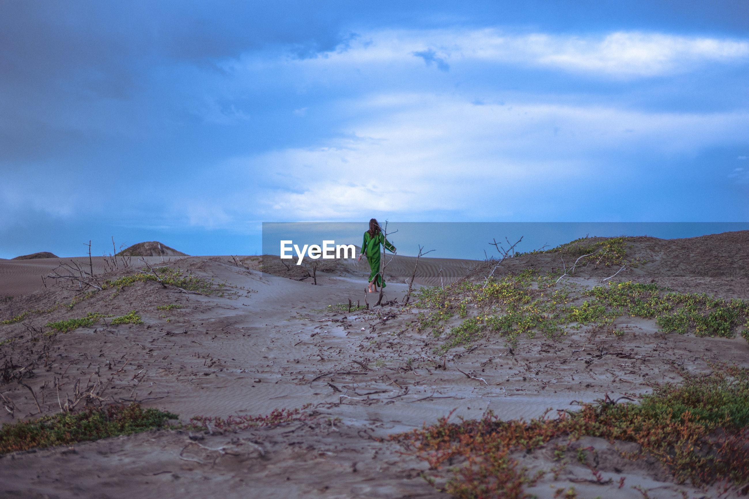 Woman walking on sand dune in desert