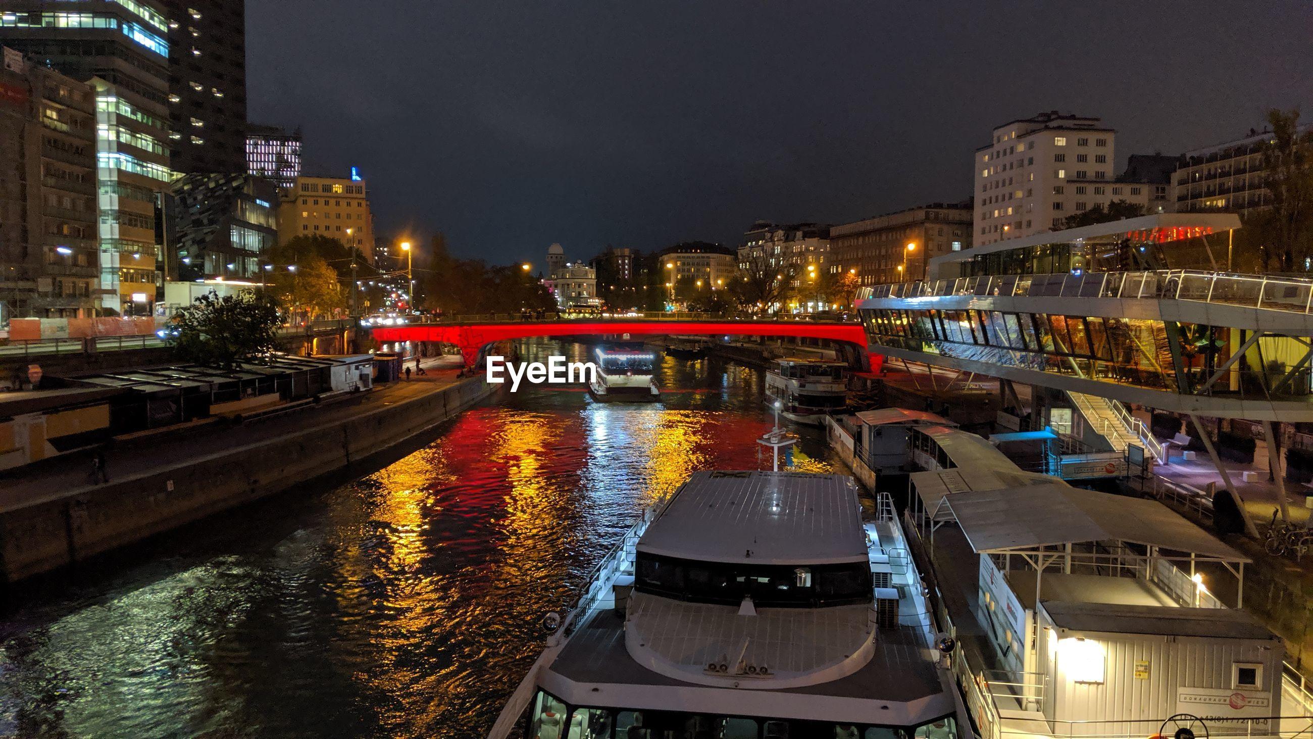 ILLUMINATED BRIDGE OVER RIVER AMIDST BUILDINGS AT NIGHT