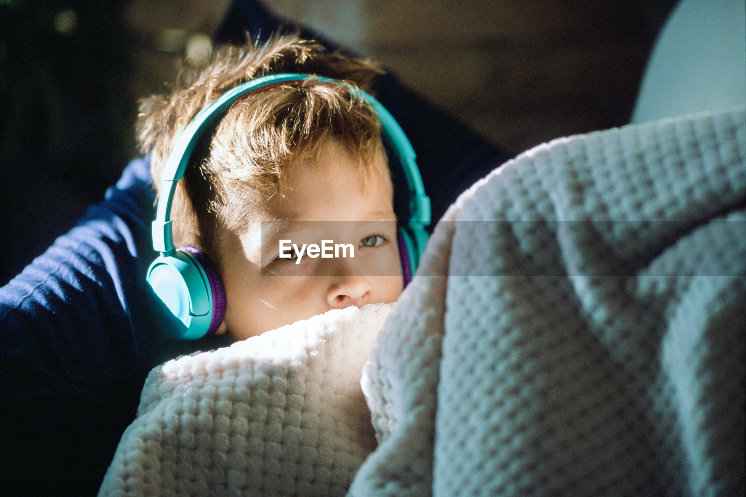 Cute boy looking away while listening music under blanket at home