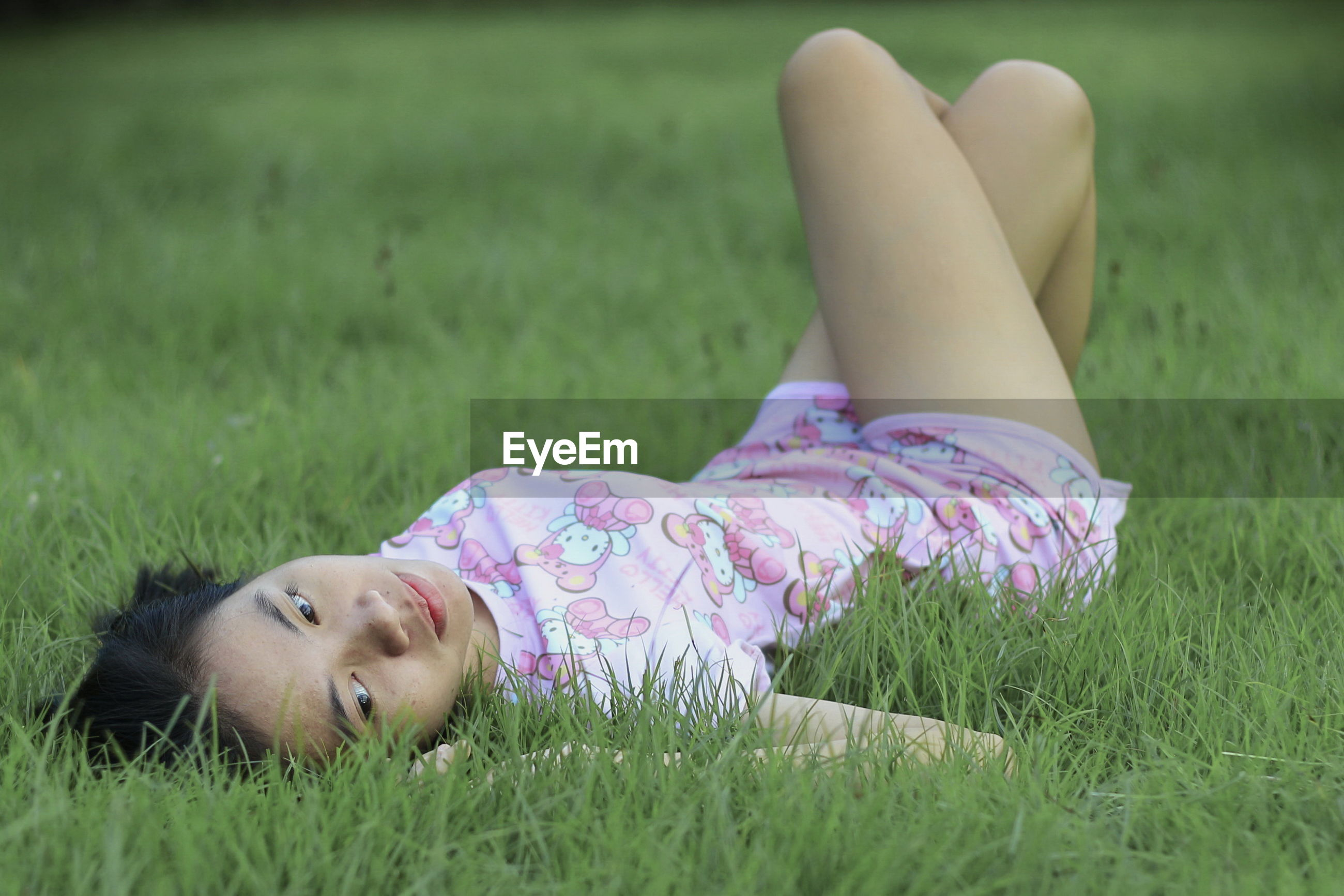 Thoughtful young woman lying on grass