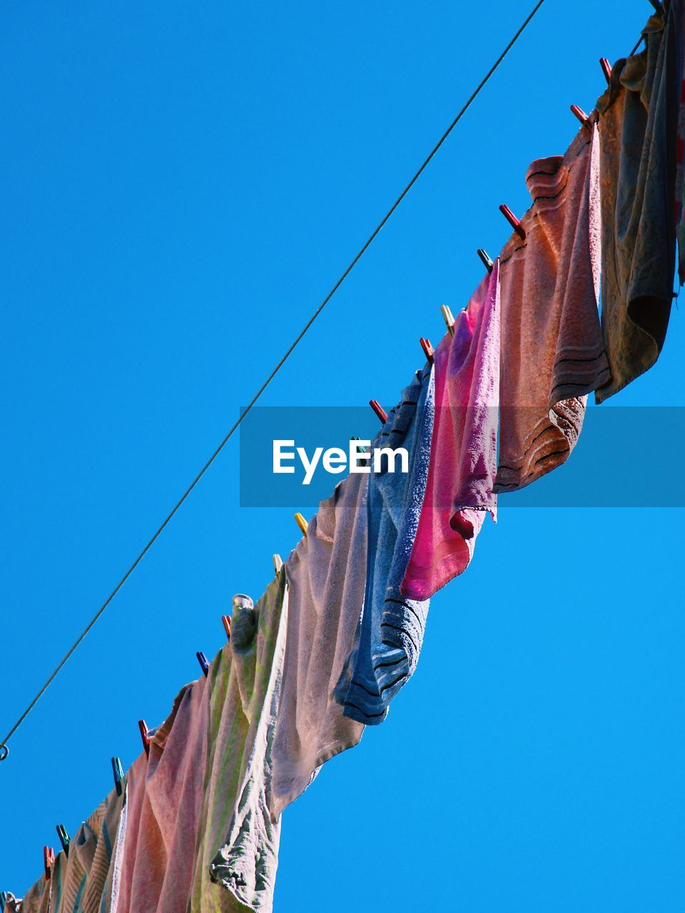 Low Angle View Of Towels Drying Against Blue Sky