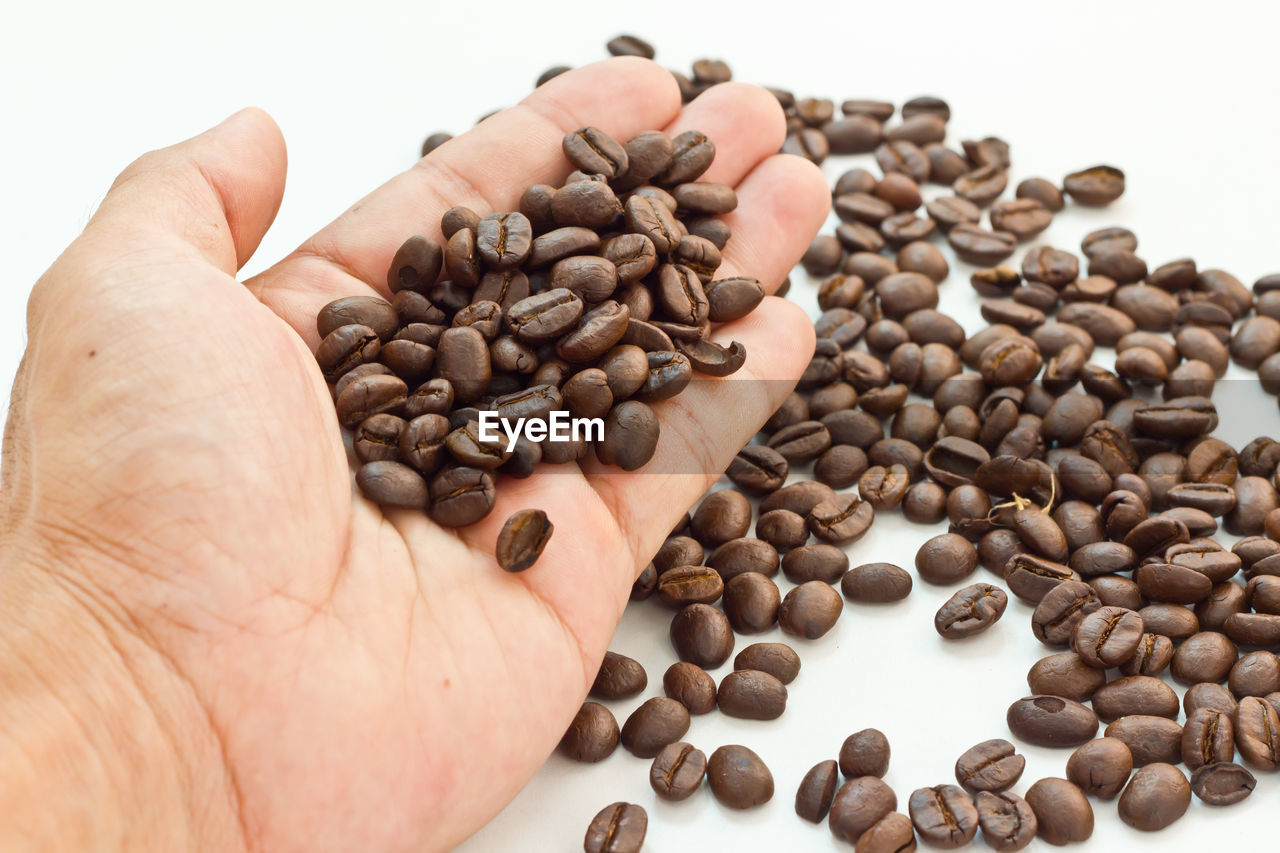 coffee bean, roasted coffee bean, food and drink, human hand, one person, raw coffee bean, brown, human body part, large group of objects, close-up, food, abundance, real people, white background, black peppercorn, freshness, indoors, day