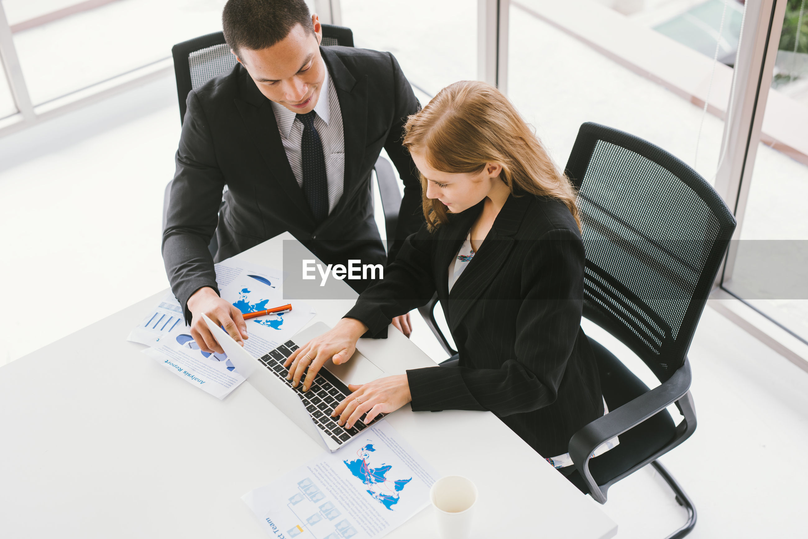 High angle view of colleagues discussing over laptop on desk while sitting in office