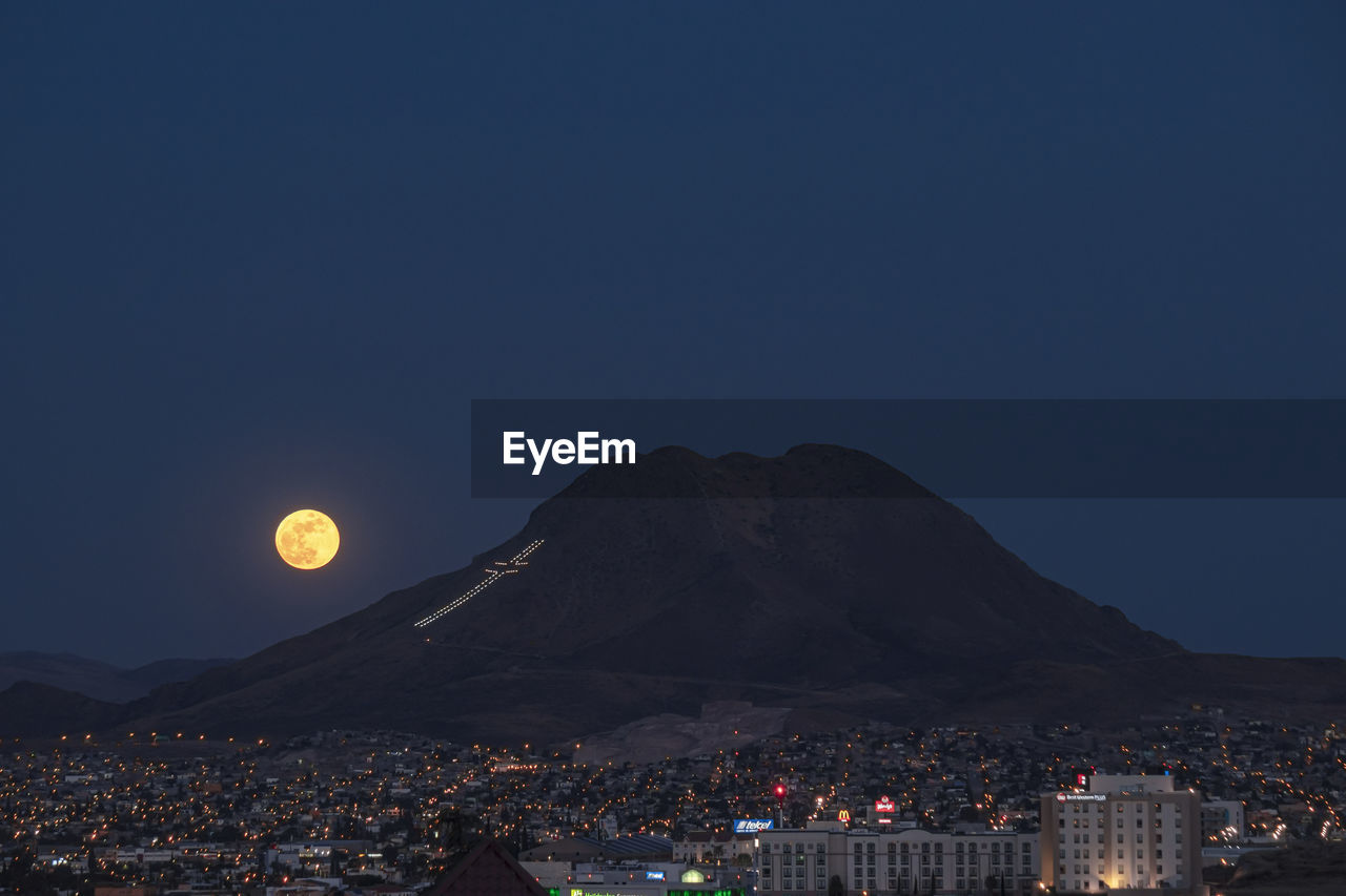 Aerial view of full moon over a city at night