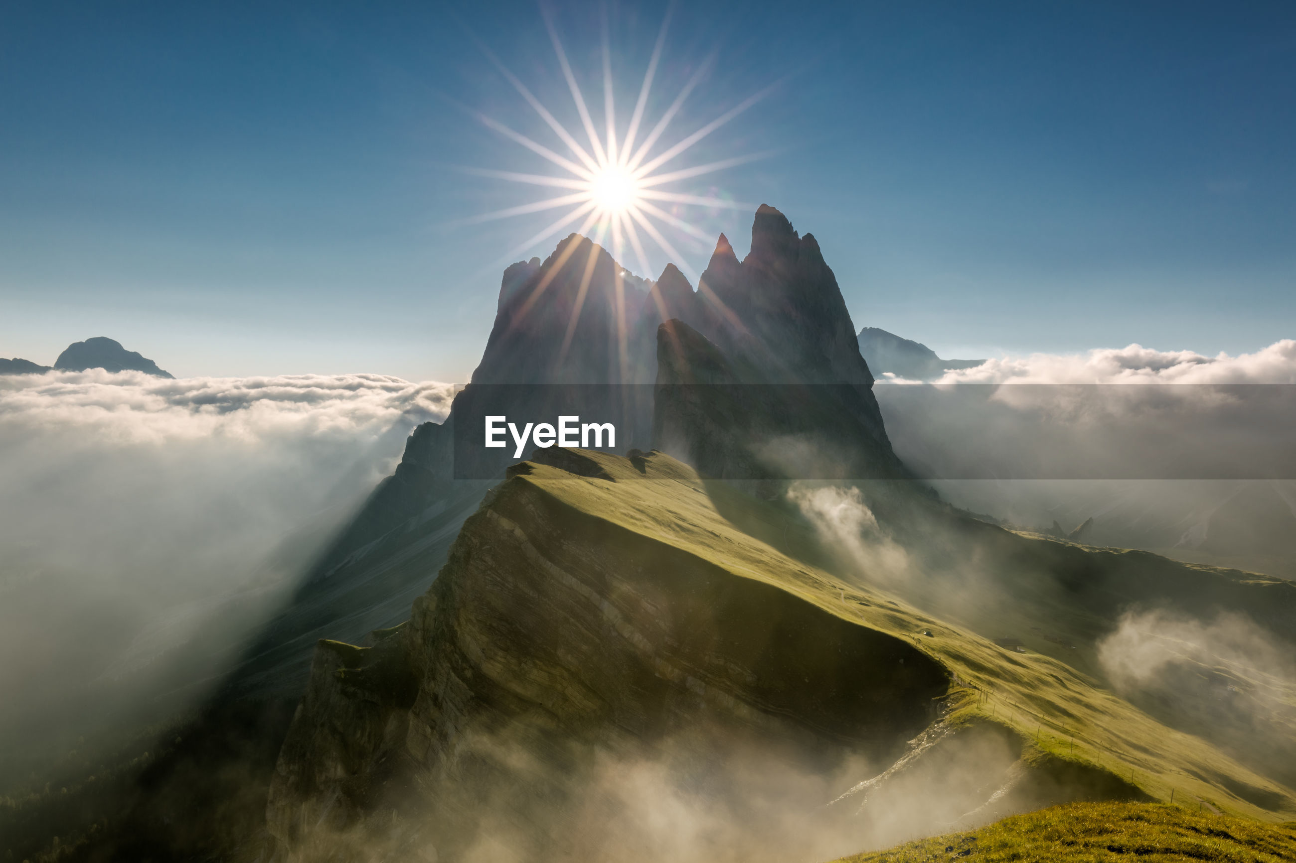Scenic view of mountains against sky in sunny day