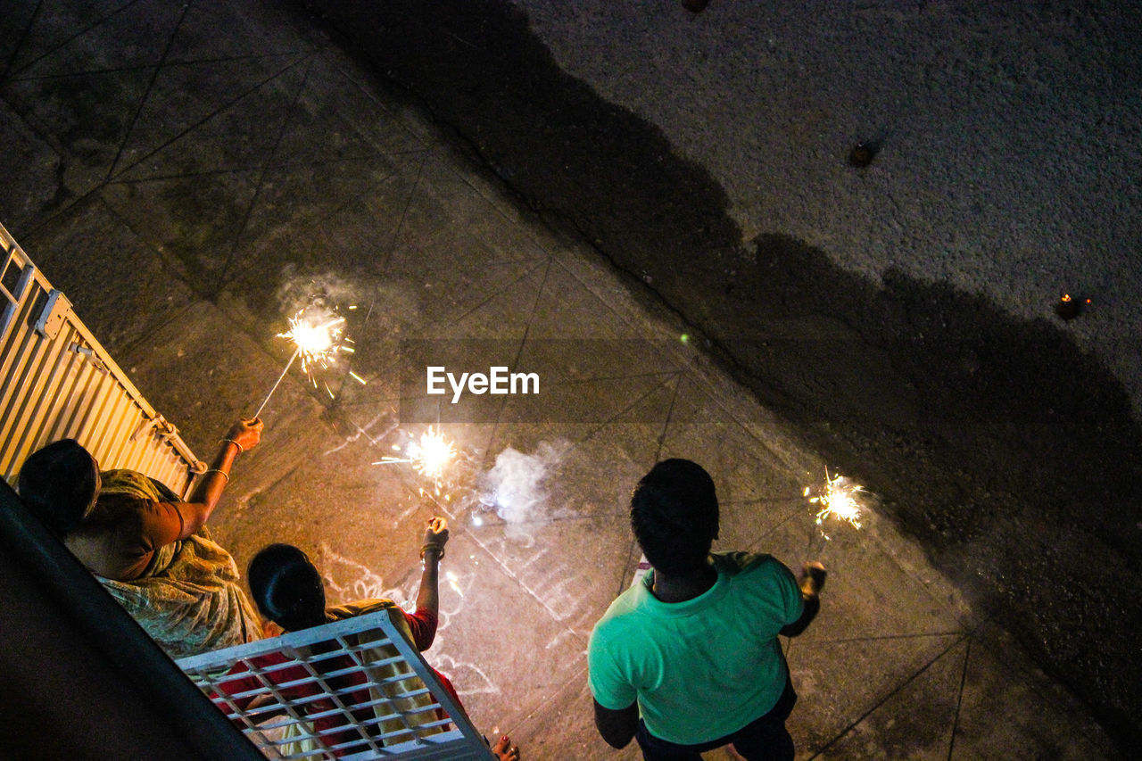 High Angle View Of People With Sparklers At Night