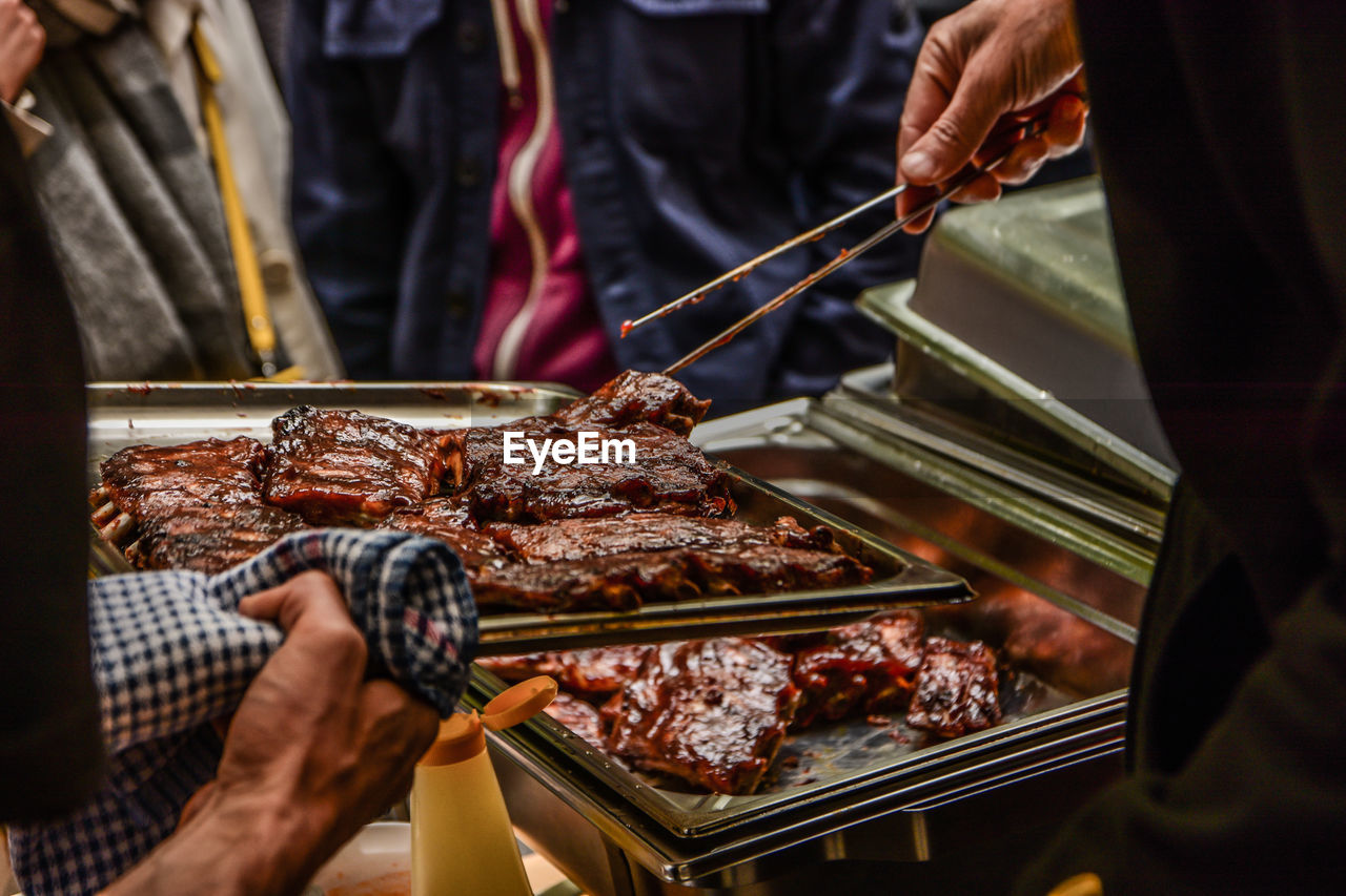 Low Angle View Of Man With Grilled Meat In Tray