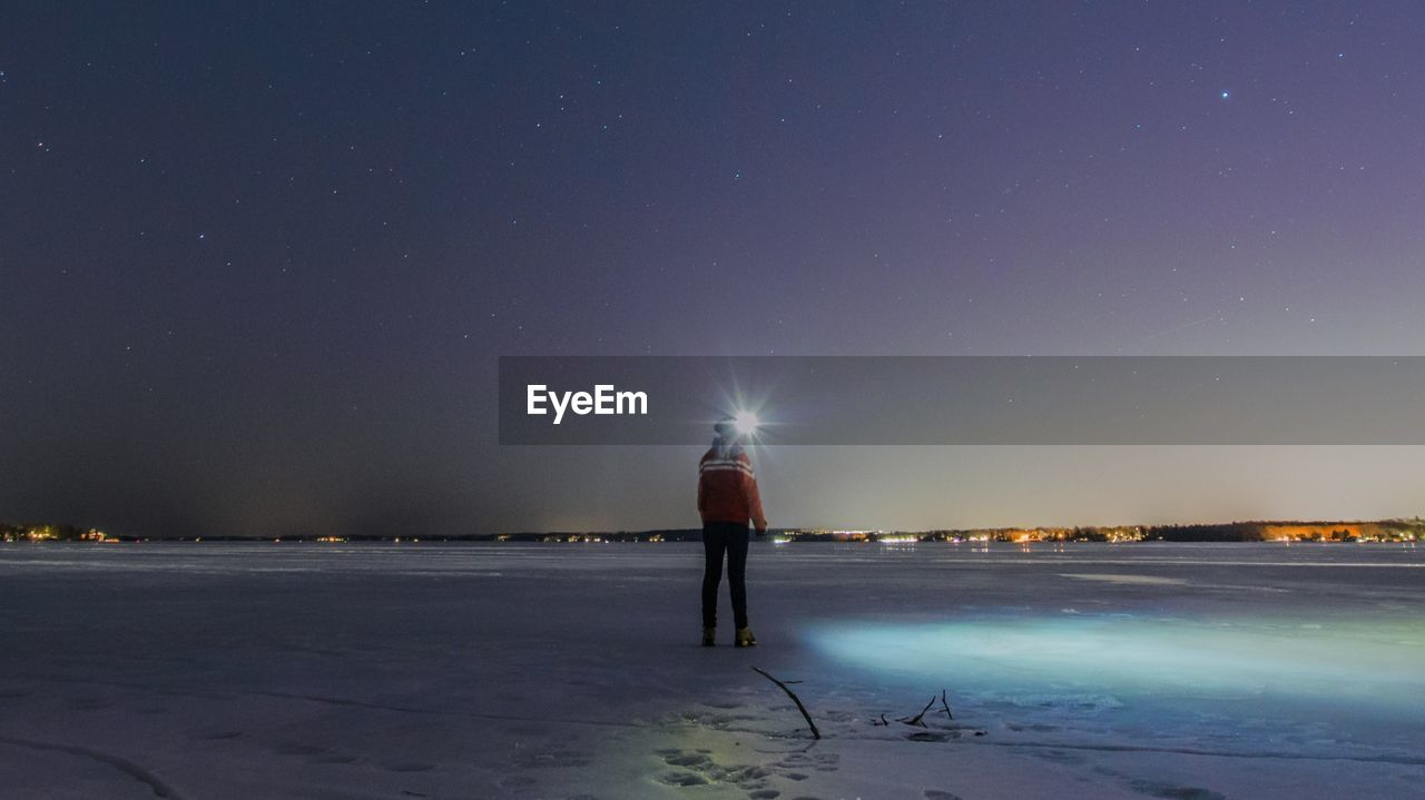 Rear View Full Length Of Person Standing On Snow Covered Landscape Against Sky At Night