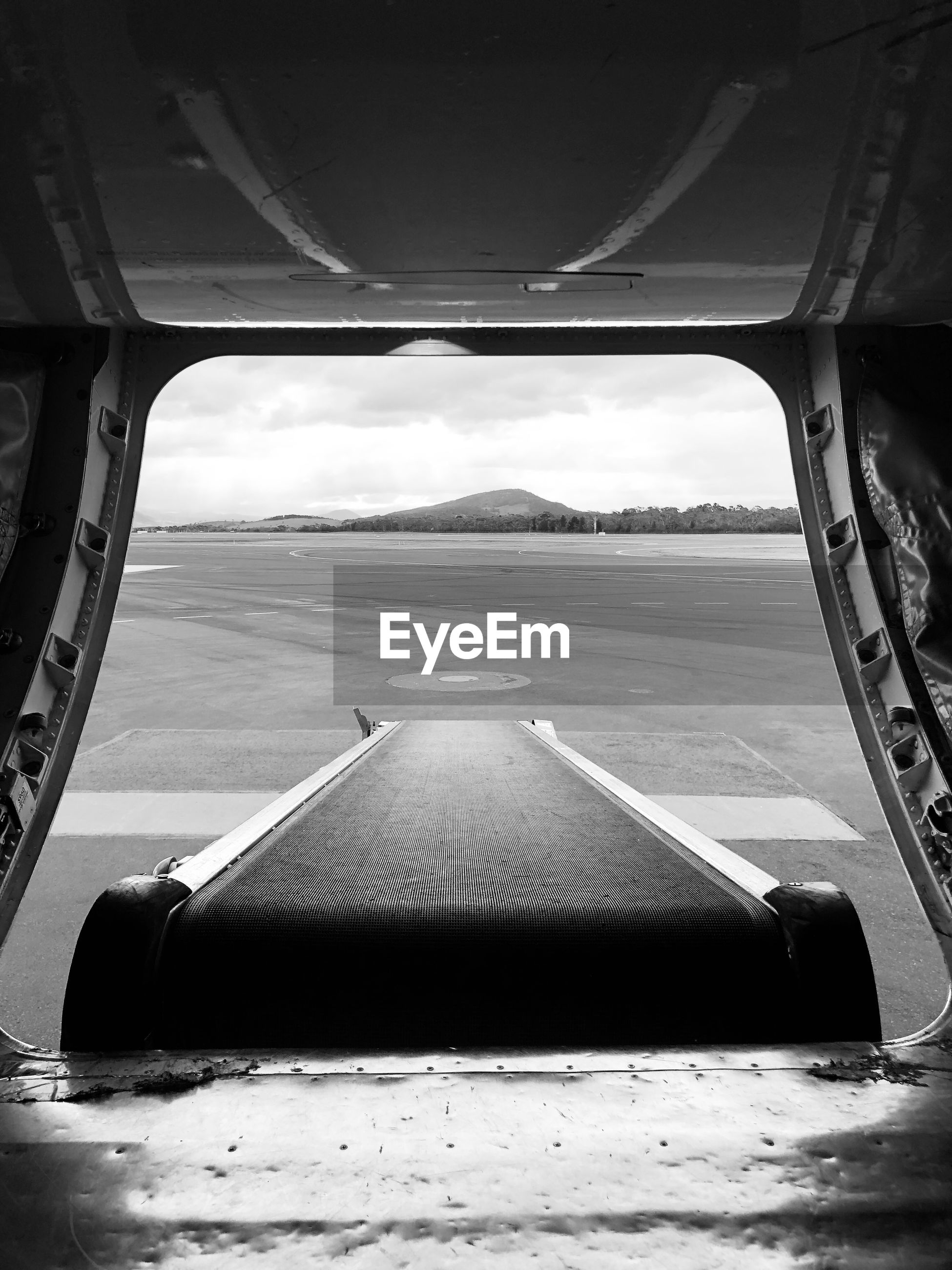 View of airport runway seen through airplane door