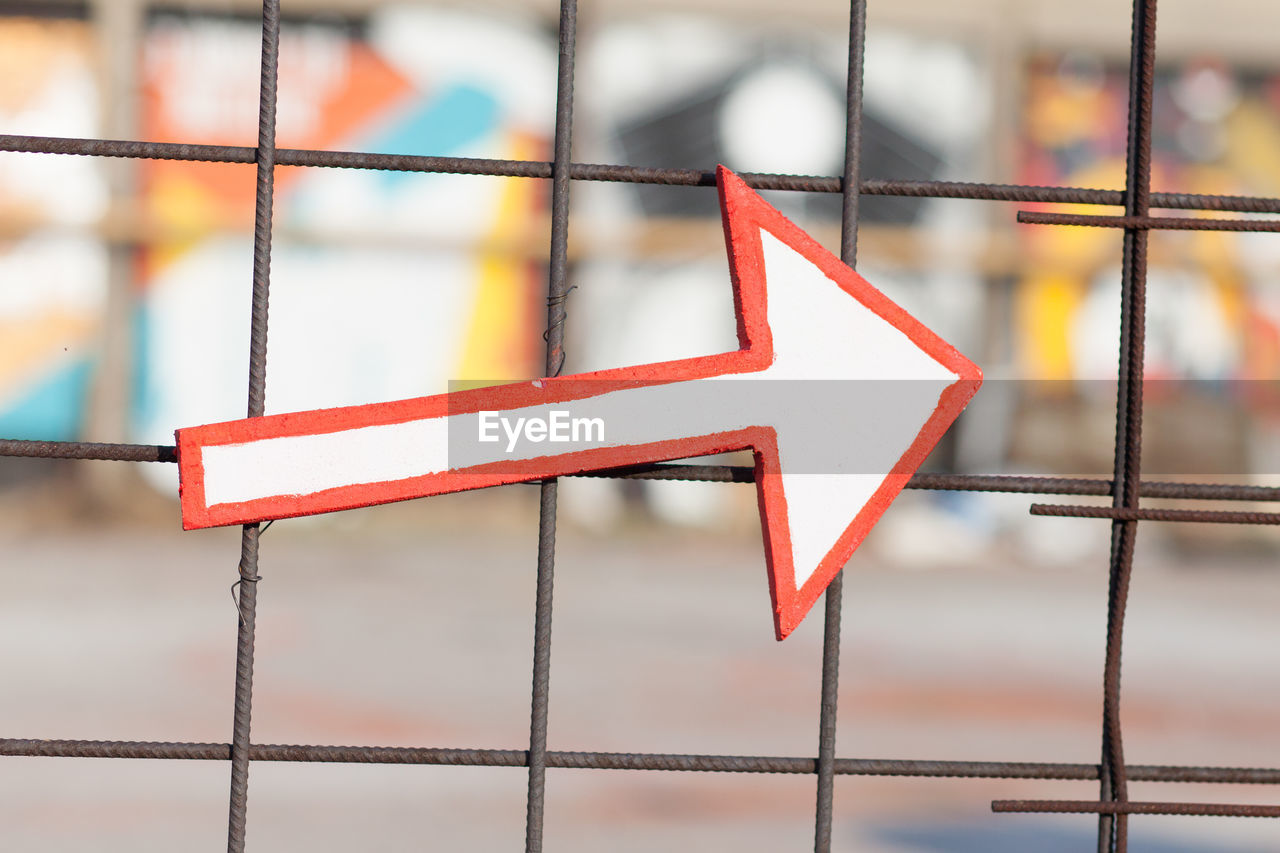 Close-Up Of Arrow Symbol On Fence