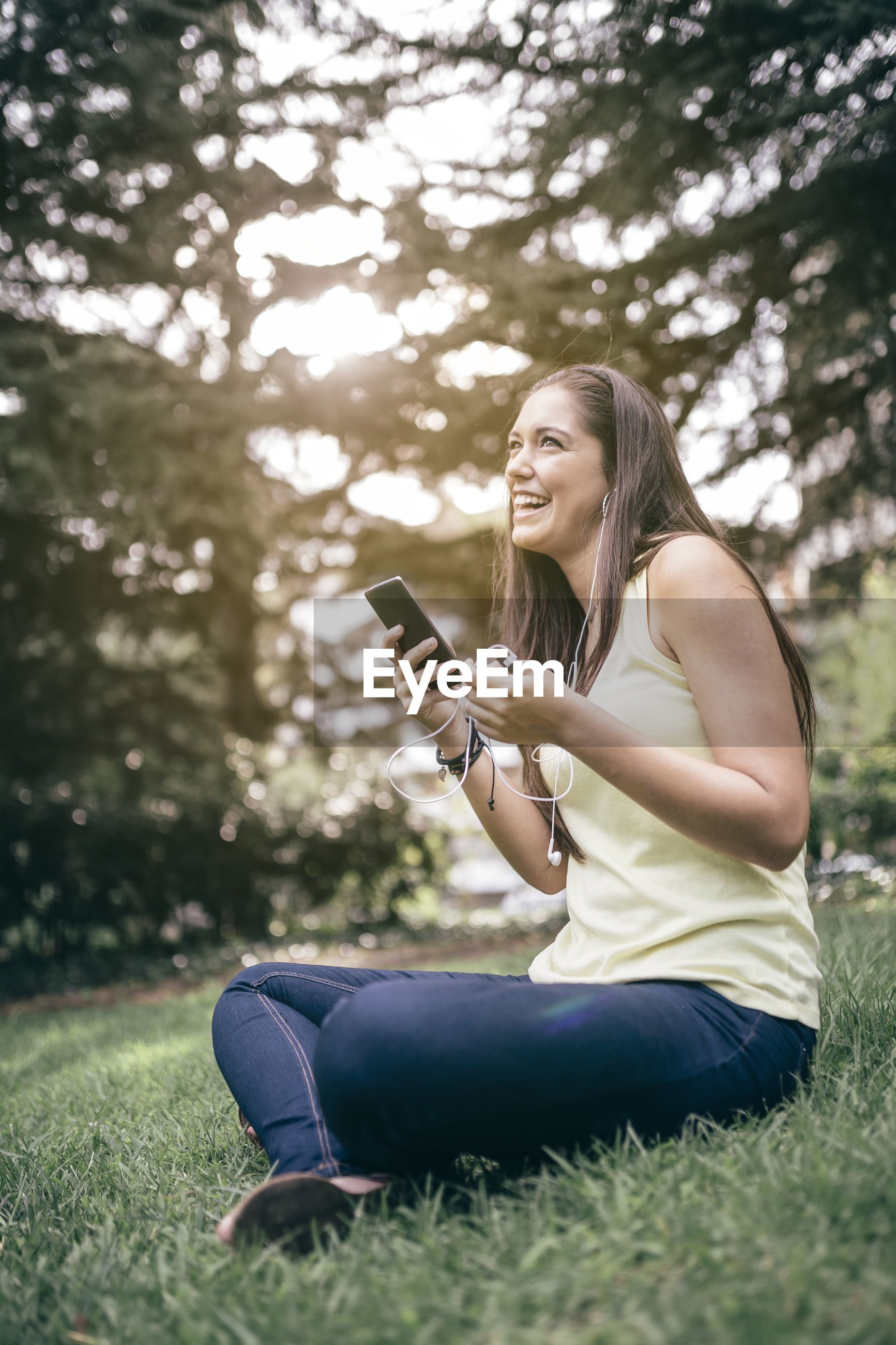 Smiling woman listening music while sitting in park