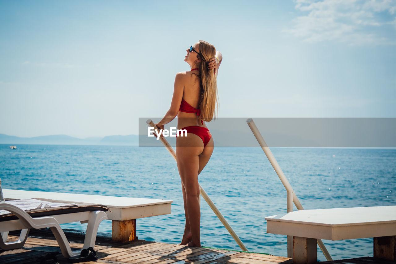 Woman in bikini standing against sea