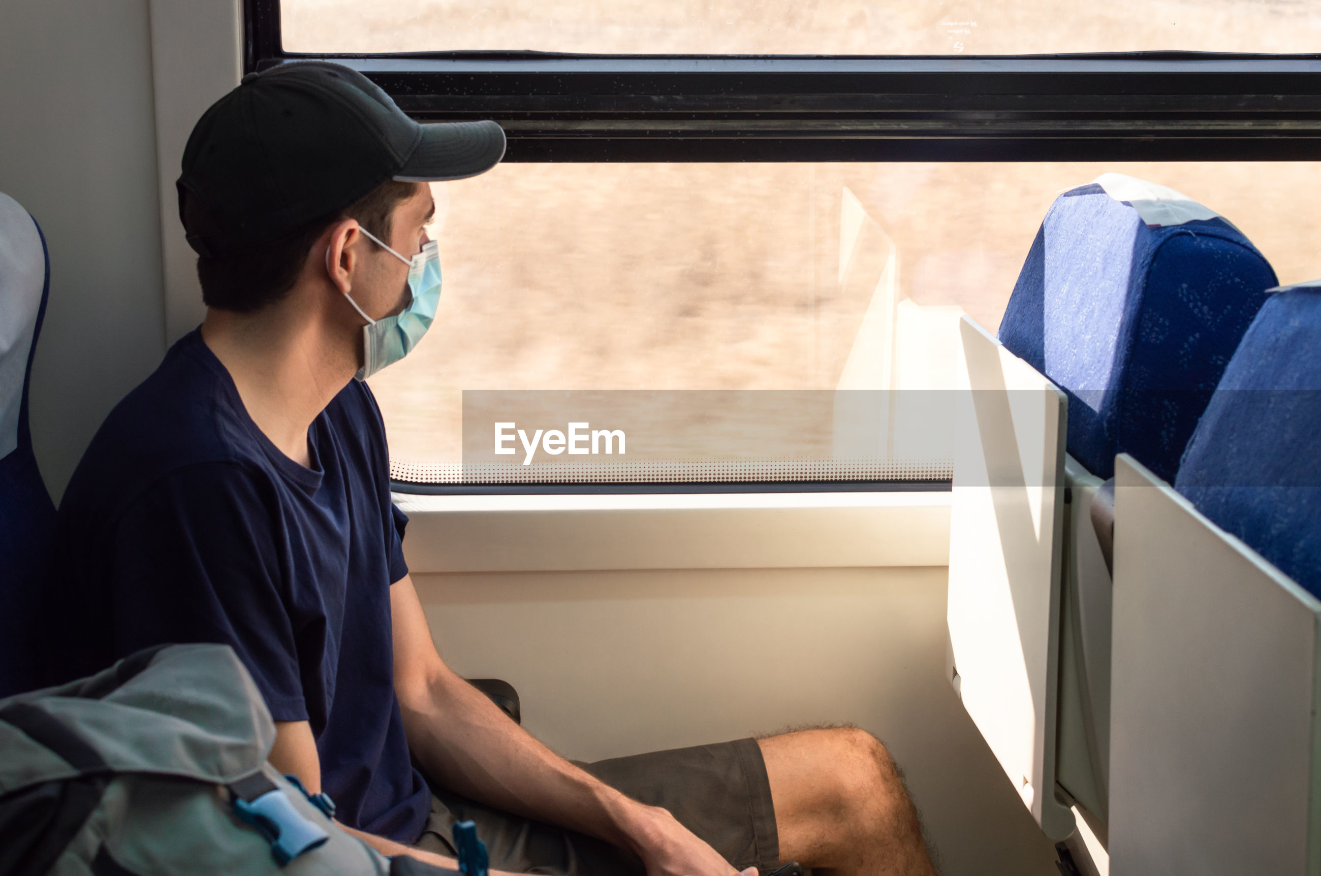 SIDE VIEW OF MAN SITTING IN TRAIN
