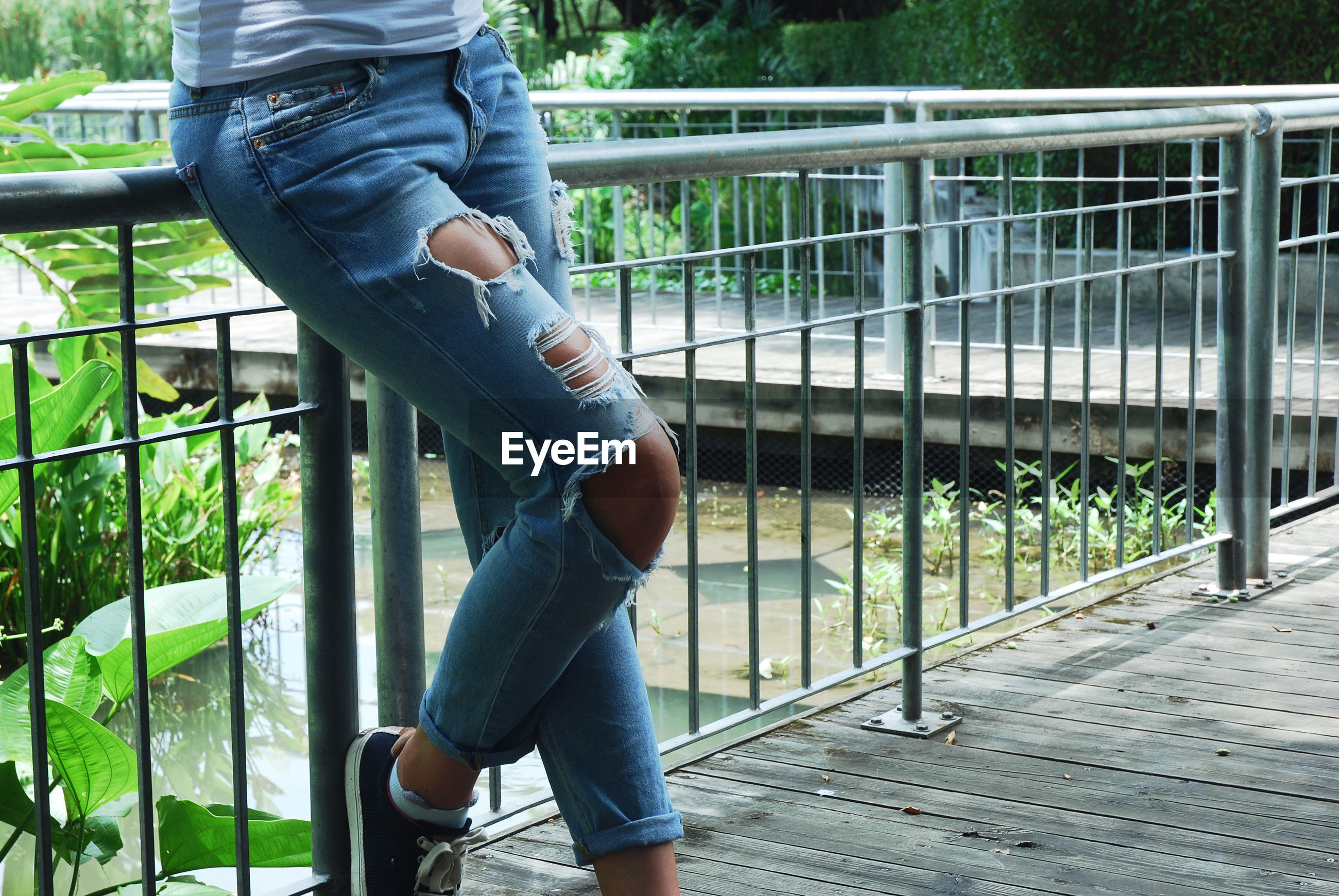 Low section of woman wearing torn jeans standing on footpath