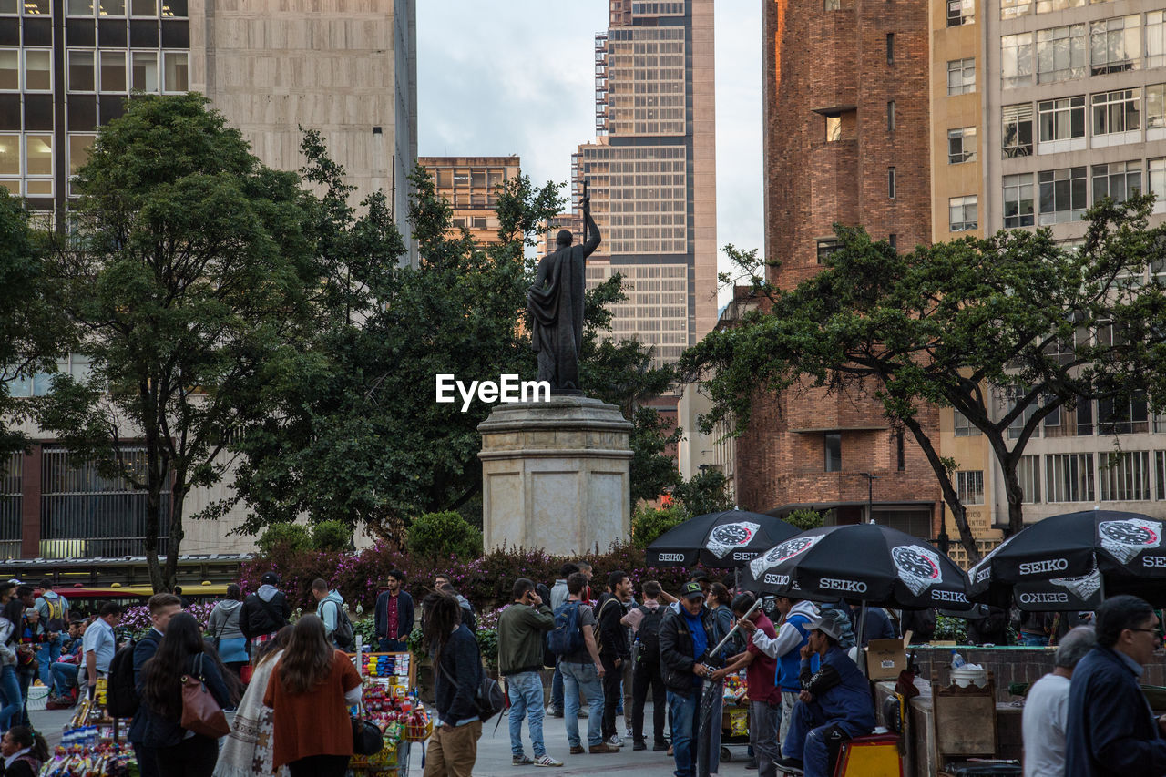 architecture, city, built structure, building exterior, crowd, large group of people, statue, group of people, sculpture, real people, representation, plant, street, art and craft, tree, human representation, city life, day, women, men, outdoors, office building exterior