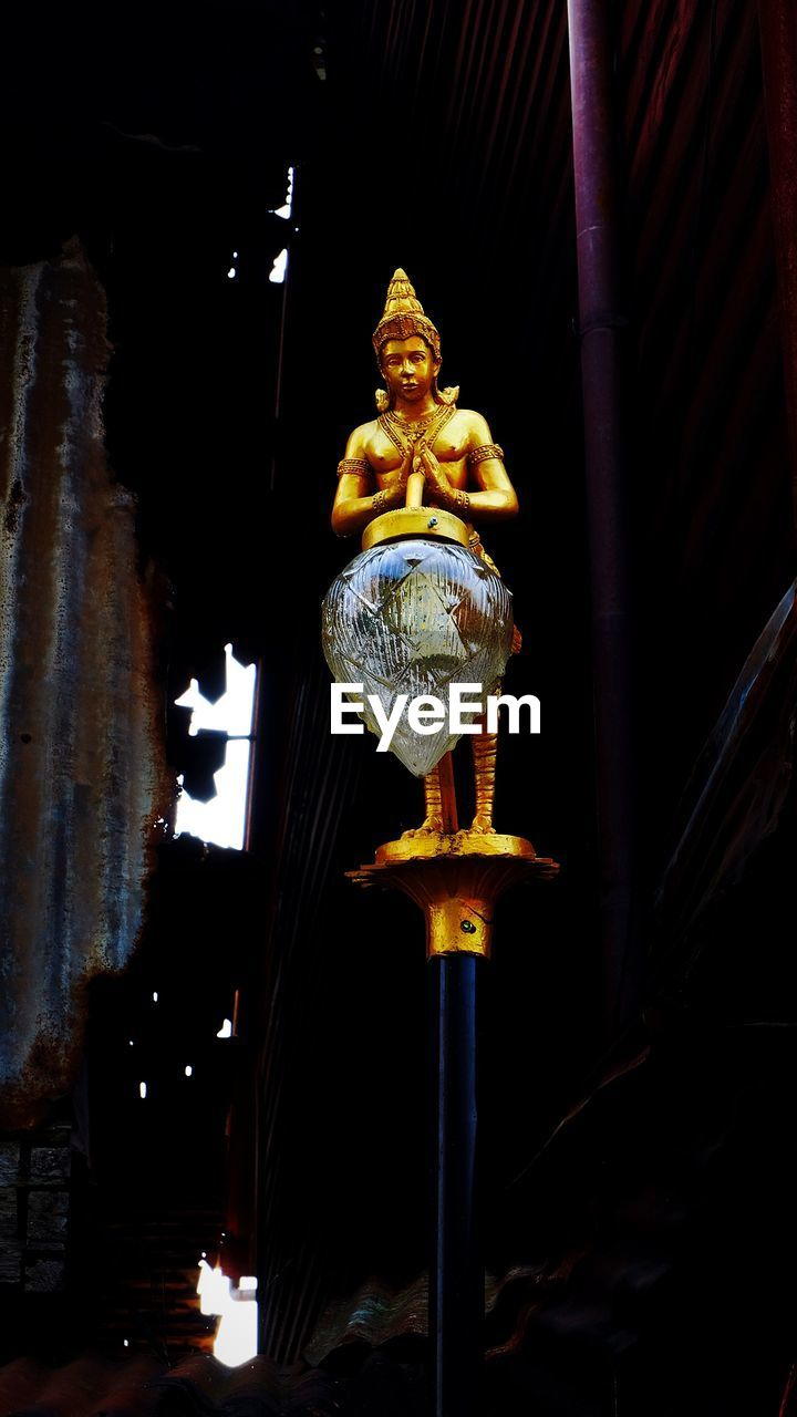art and craft, human representation, representation, statue, architecture, male likeness, sculpture, creativity, spirituality, belief, built structure, no people, religion, low angle view, craft, night, place of worship, illuminated, lighting equipment, building, architectural column, ornate
