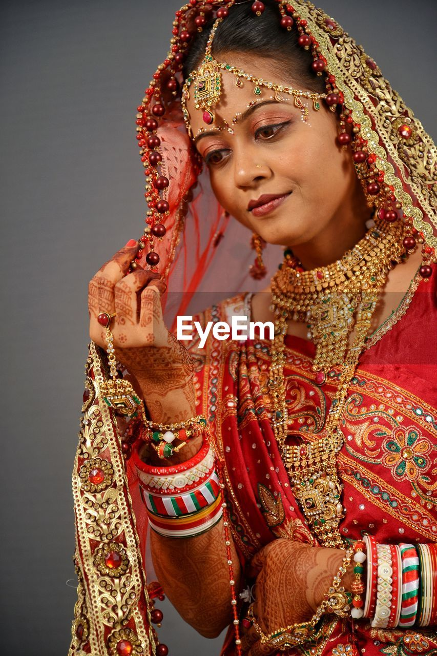 traditional clothing, front view, one person, young women, young adult, clothing, lifestyles, real people, women, indoors, adult, smiling, sari, newlywed, beautiful woman, bride