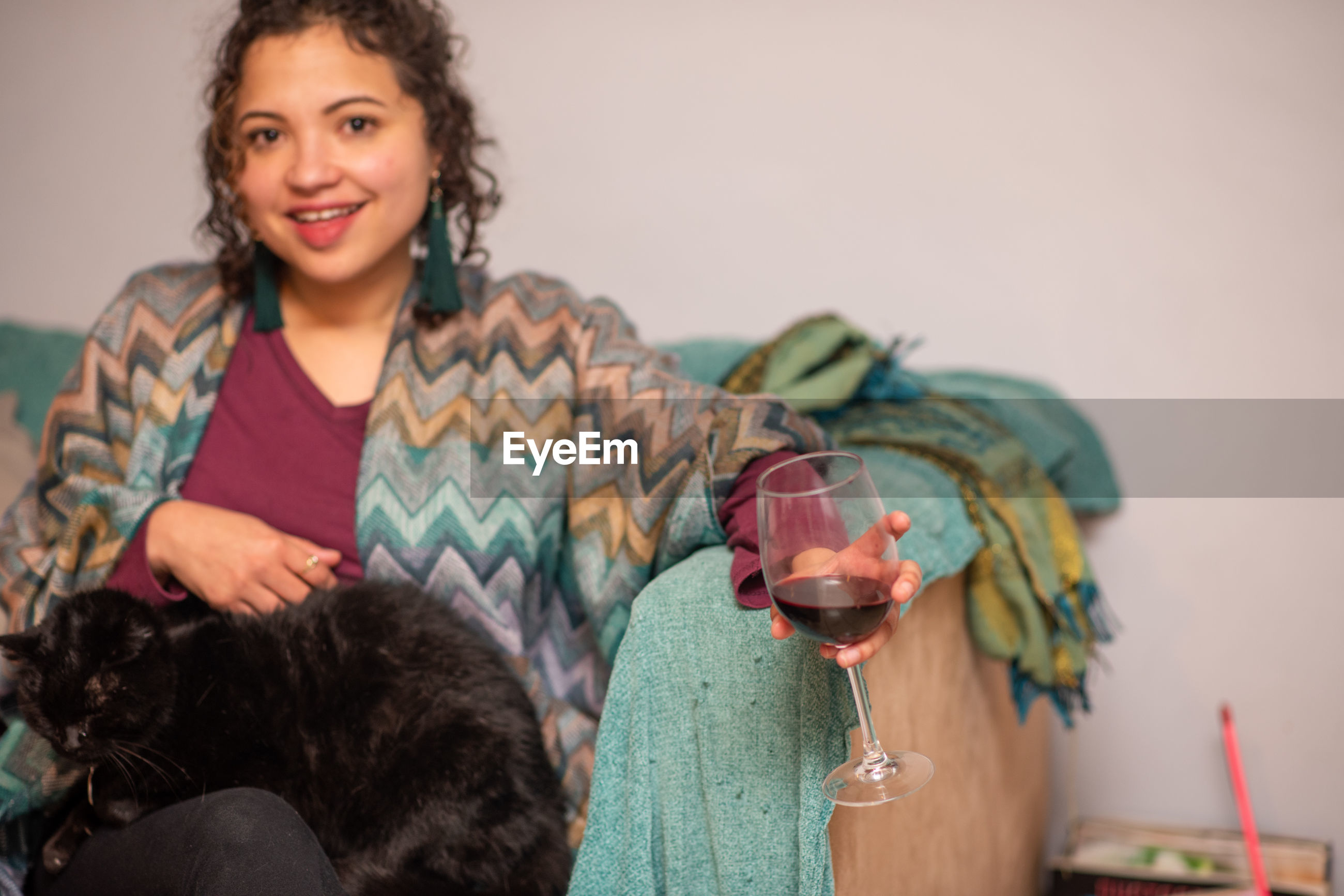 Portrait of smiling woman holding drink while sitting with cat
