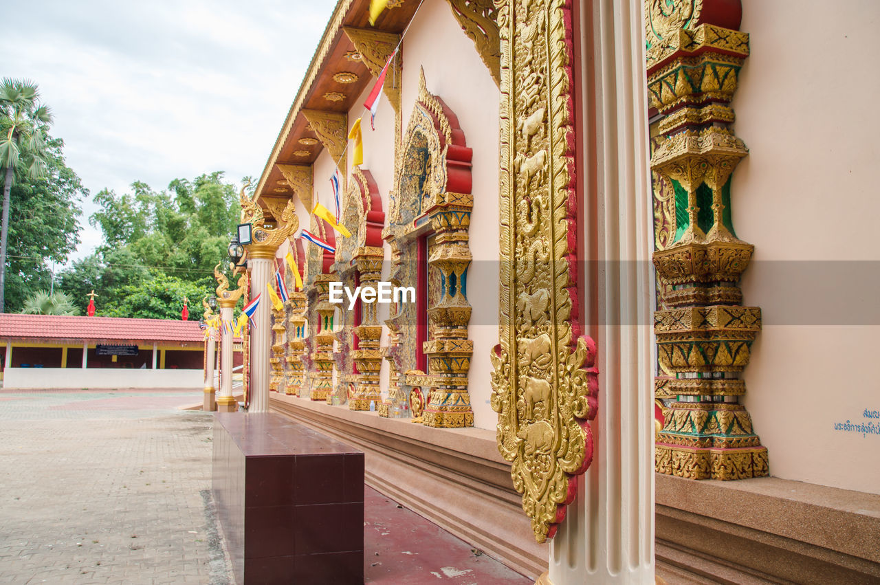built structure, architecture, building, religion, place of worship, belief, spirituality, building exterior, no people, day, travel destinations, architectural column, sky, gold colored, nature, art and craft, plant, tree, ornate