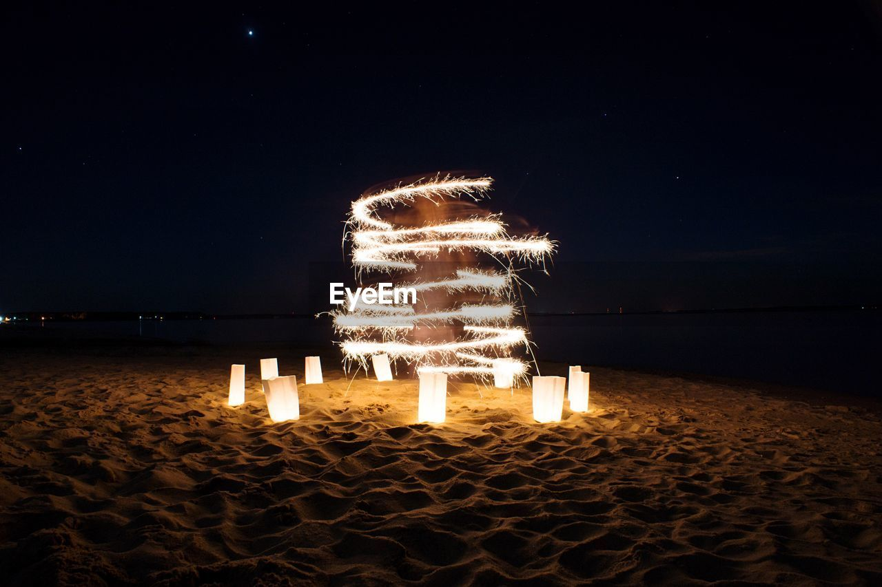 Light paintings with lamps on beach against clear sky