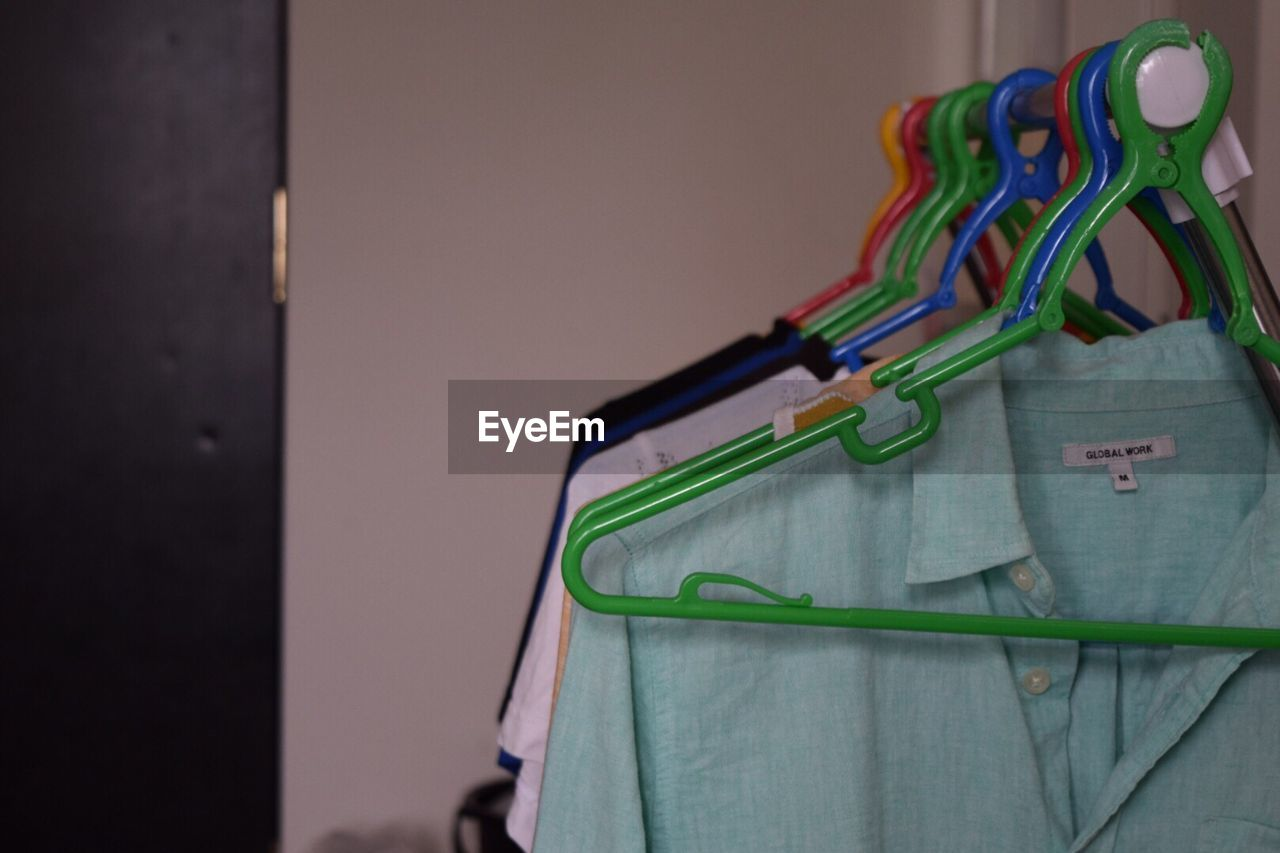 hanging, indoors, no people, close-up, focus on foreground, coathanger, day