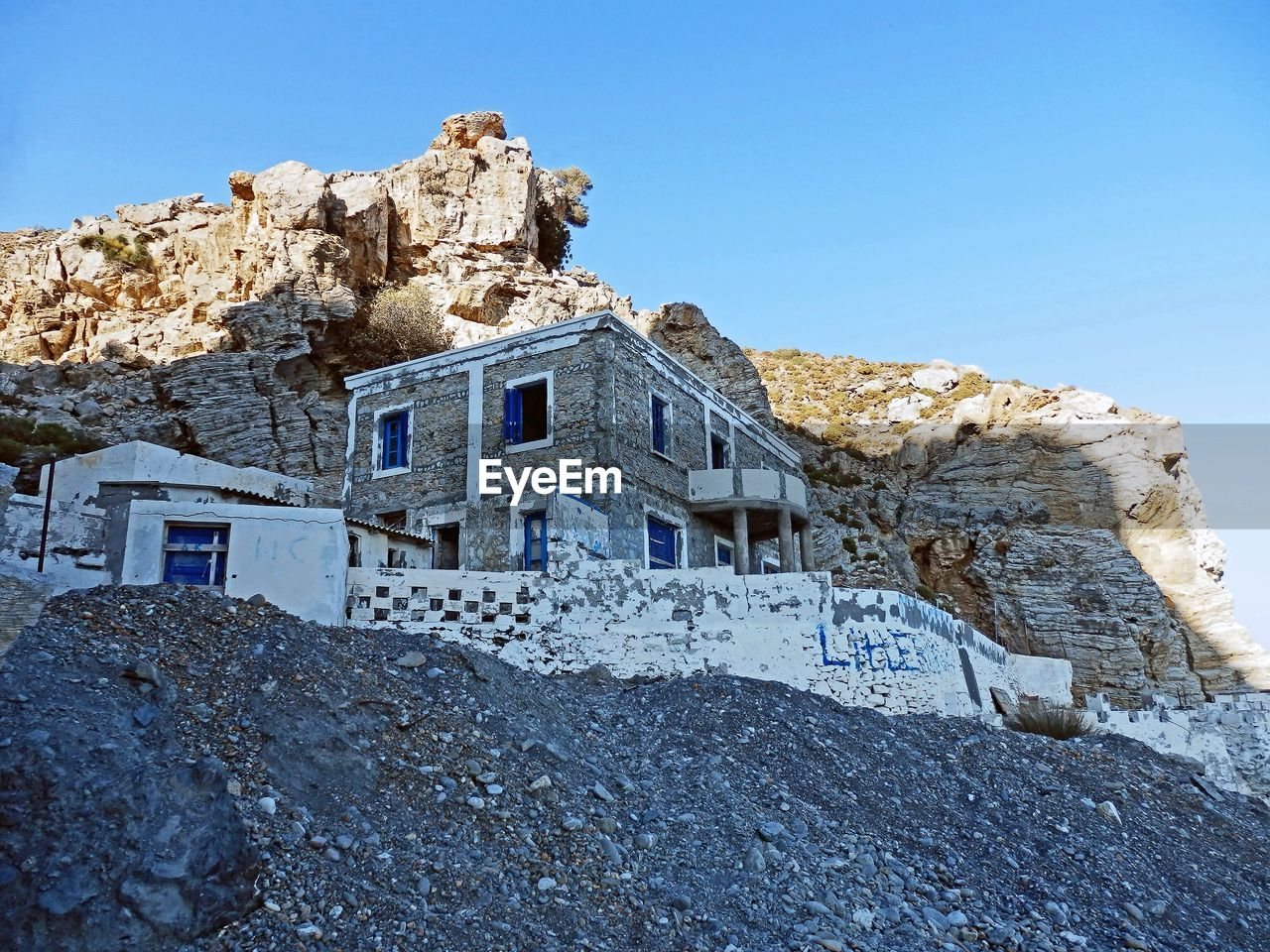 architecture, mountain, built structure, low angle view, rock - object, no people, house, building exterior, clear sky, outdoors, day, nature, blue, sky, scenics, beauty in nature