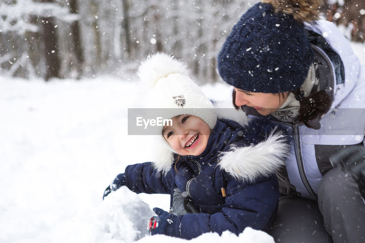 MOTHER WITH DAUGHTER IN SNOW